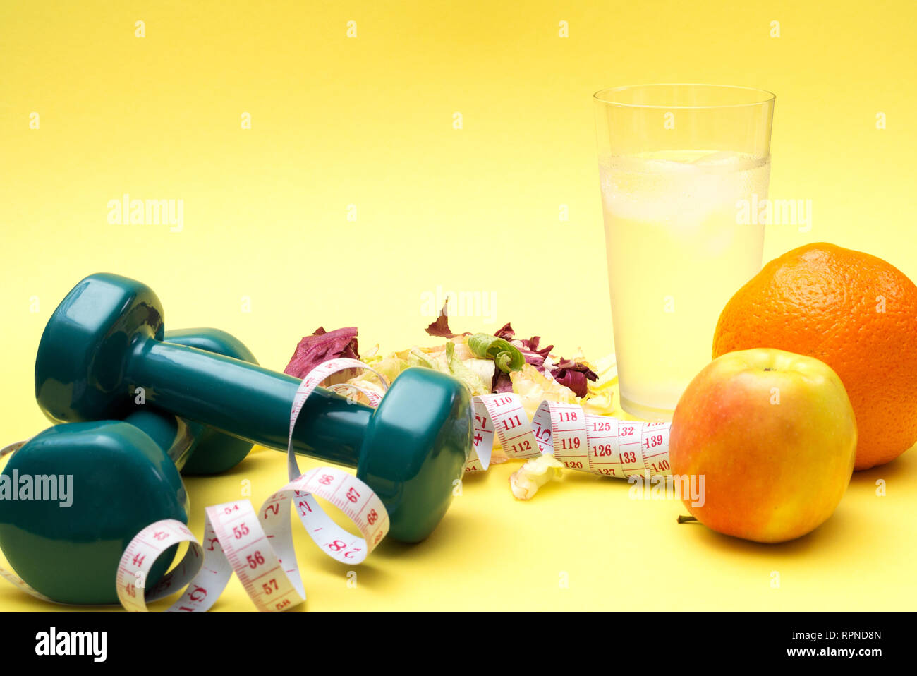 Dumbbells for sports. Fitness salad and tape measure on a yellow table. Oranges, apples and clear water with ice for the concept of a healthy lifestyl - Stock Image