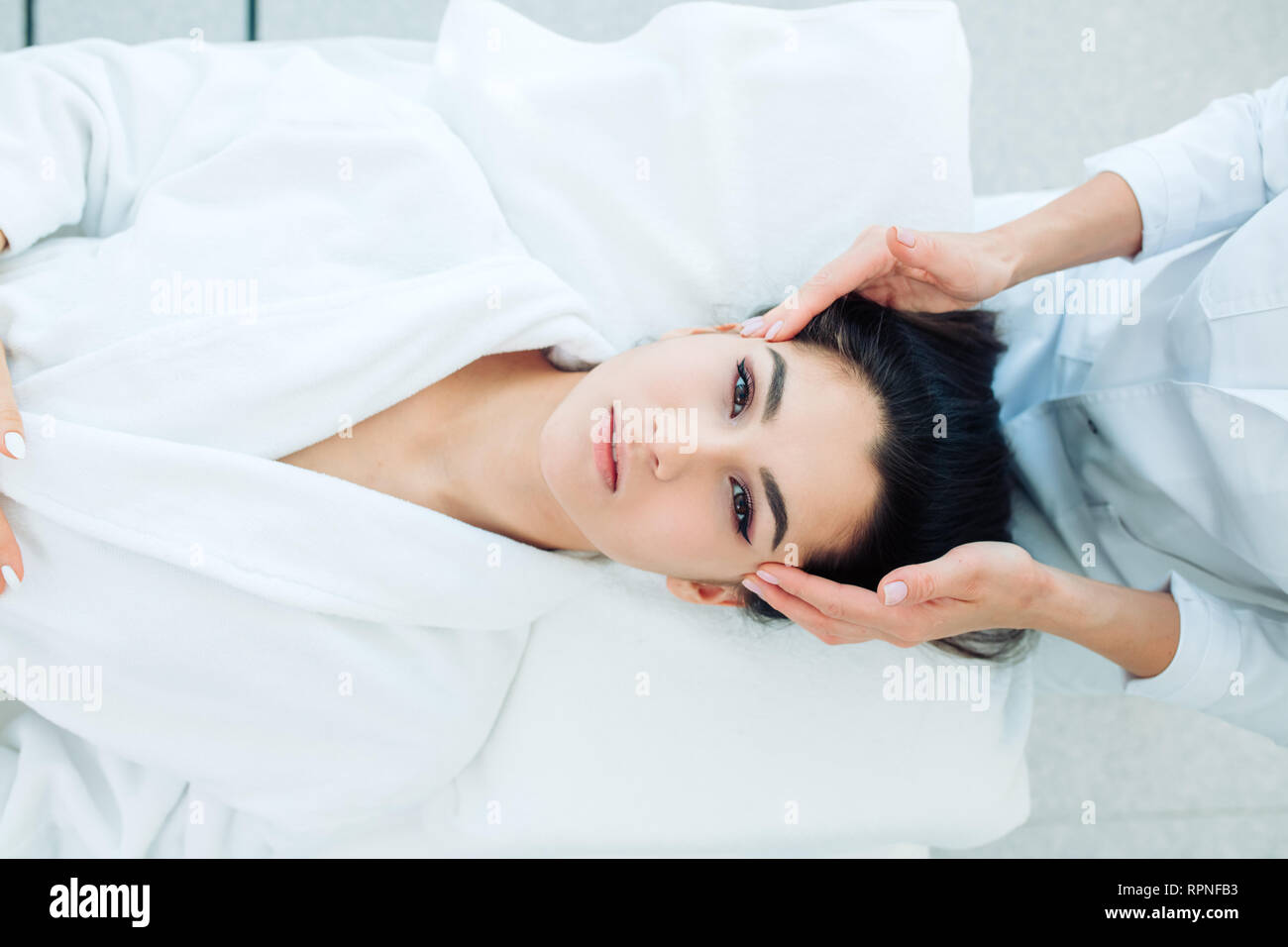 Facial spa cosmetology procedure, top view. Skin care lift anti age massage. Caucasian brunette woman dressed in white bathrobe, receiving anti-wrinkl - Stock Image