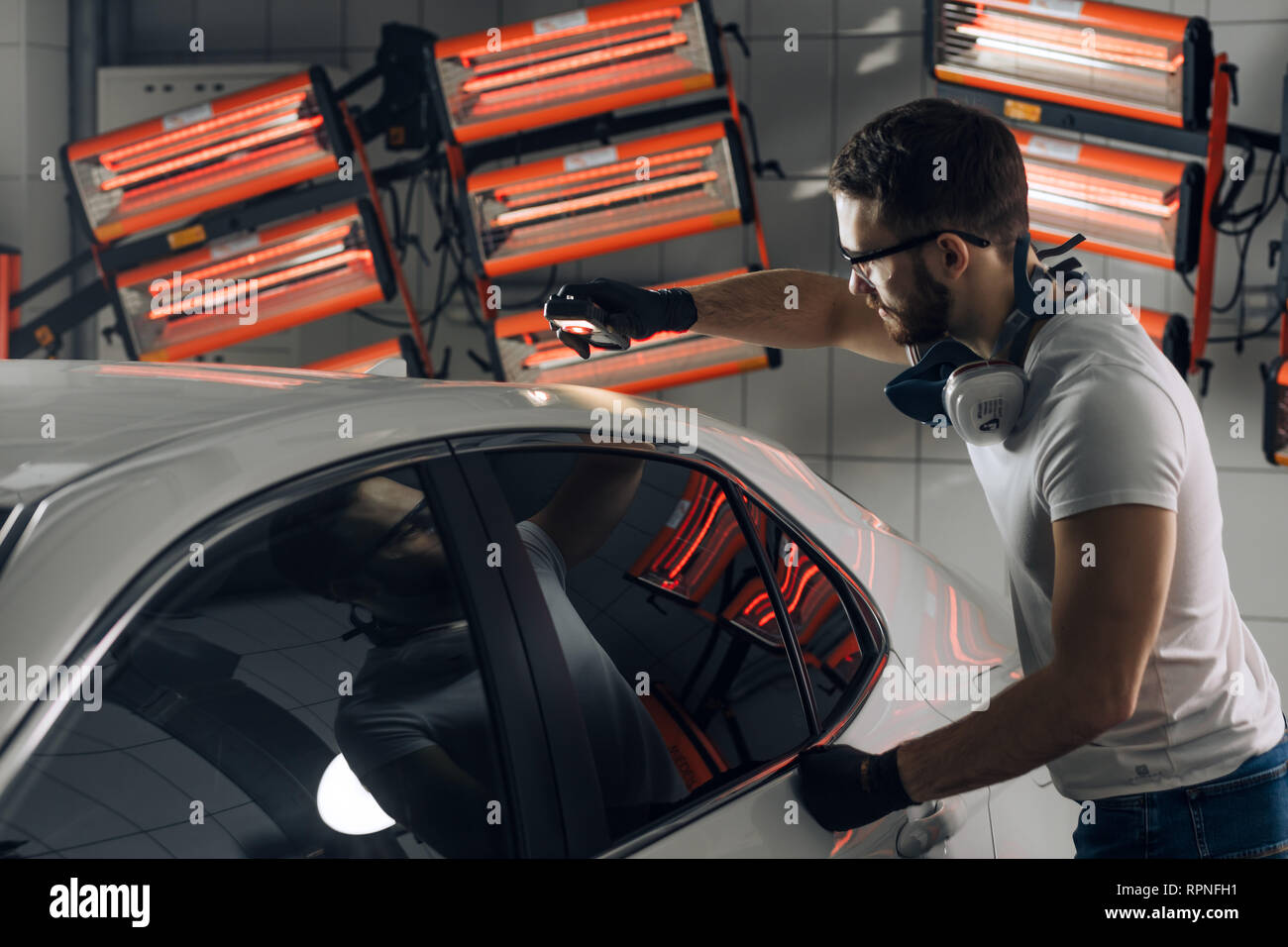 guy using a car paint thickness checker at workplace at the garage. close up photo Stock Photo