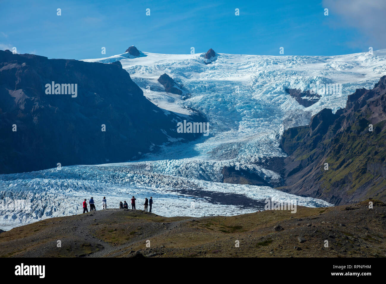 People dwarfed beneath the ice fall of Kviarjokulll glacier. Vatnajokull ice cap, Sudhurland, south east Iceland. - Stock Image