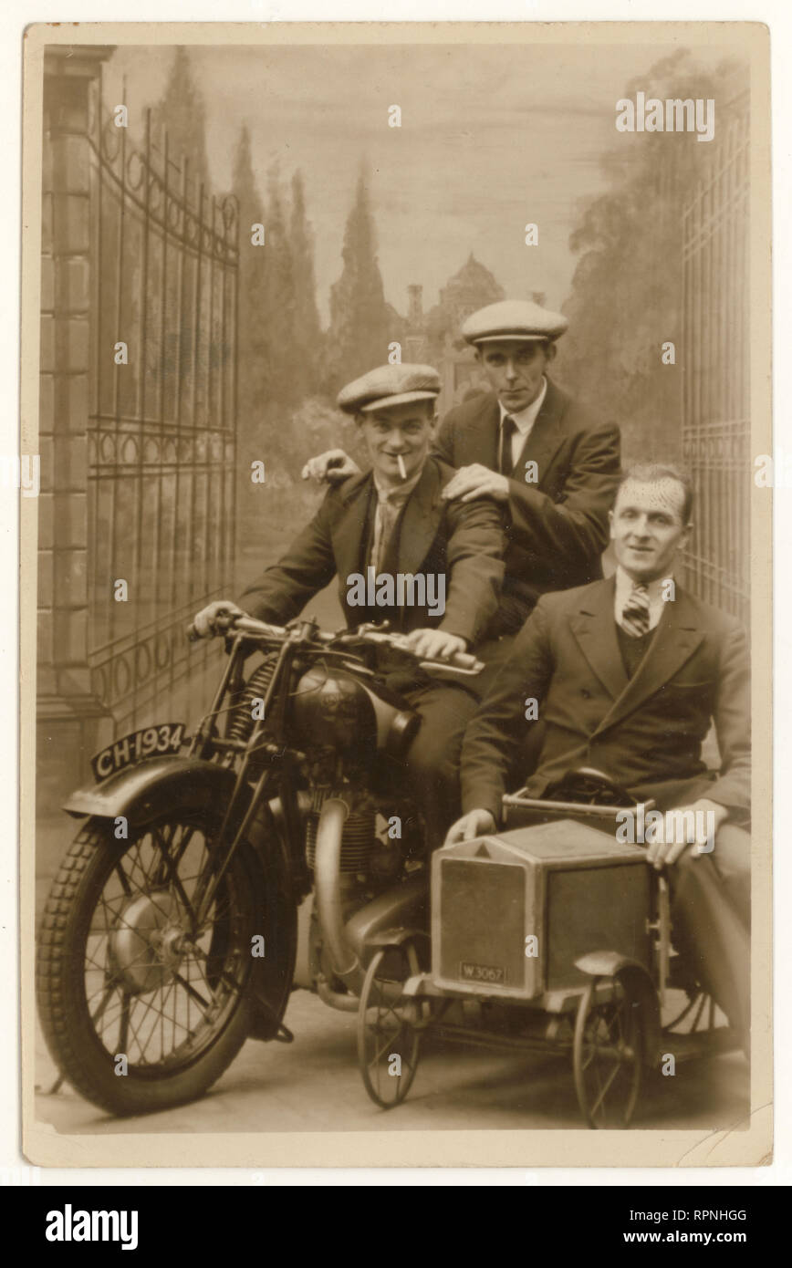 1930's postcard studio portrait of happy men wearing suits and flat caps, posing on motorbike prop, enjoying their annual holiday or leave, dated 20 October 1934, Blackpool, Lancashire, U.K. - Stock Image