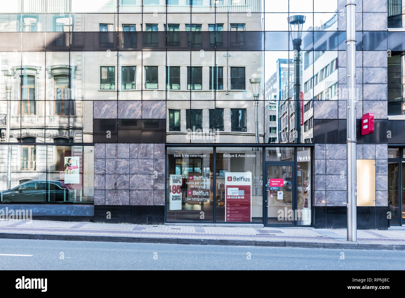 City of Brussels / Belgium - 02 15 2019: Facade of a large Belfius banking and insurance agency with steel and glass, reflecting the oppositie side of - Stock Image