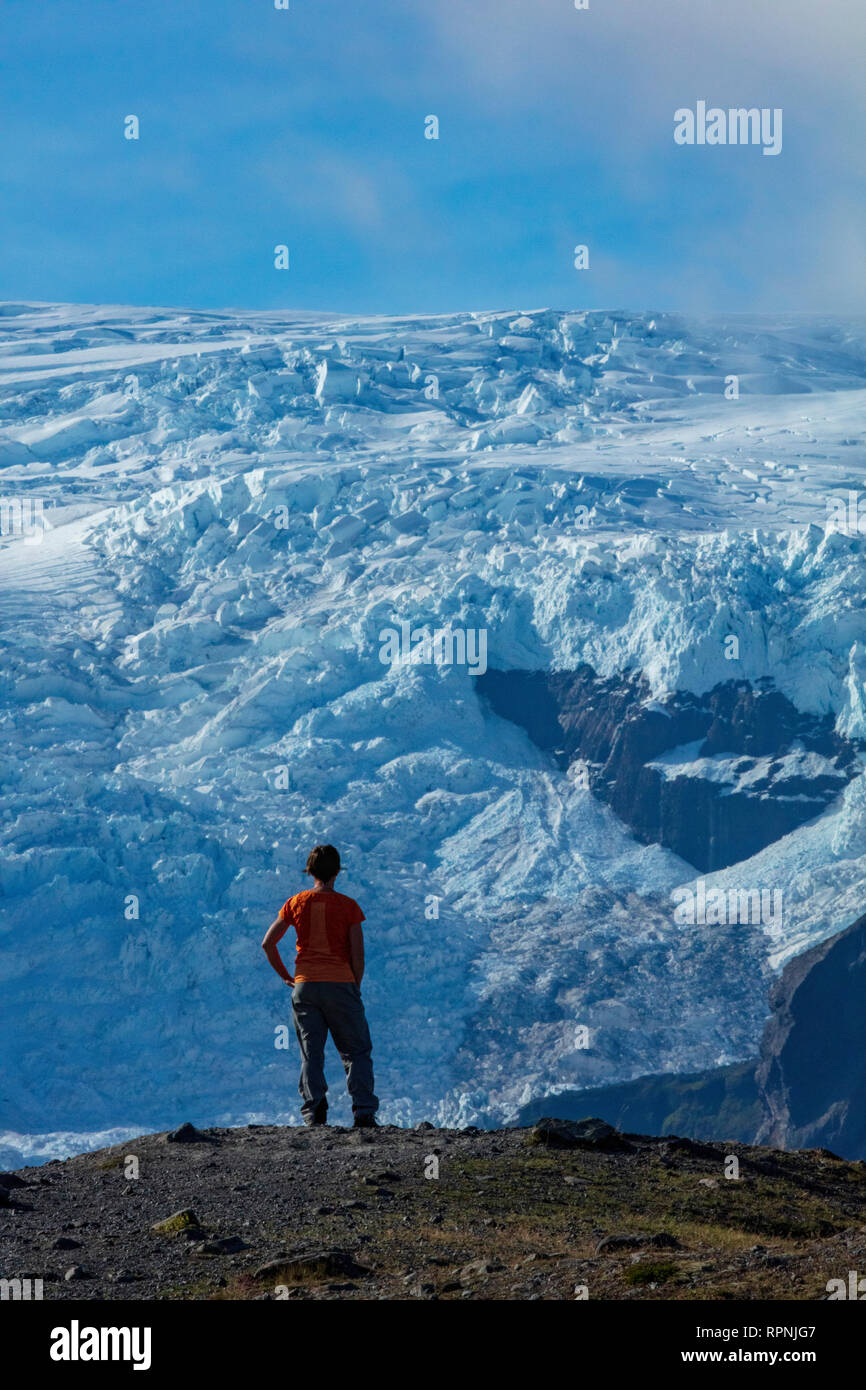 Person beneath the ice fall of Kviarjokull glacier. Vatnajokull ice cap, Sudhurland, south east Iceland. - Stock Image