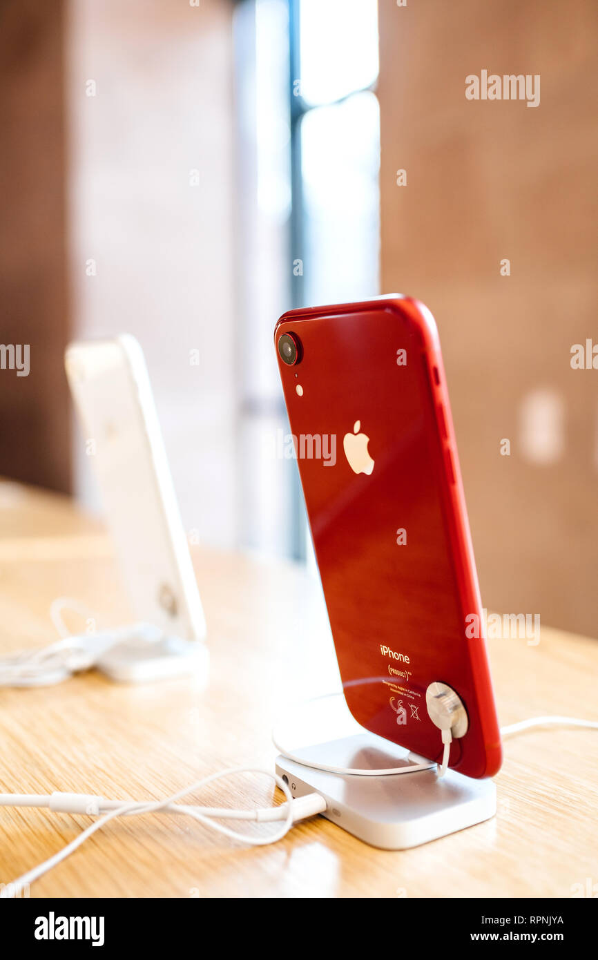 PARIS, FRANCE - OCT 26, 2018: Side view of glossy red latest iPhone XR smartphone in Apple Store Computers during the launch day - shiny silver logotype Stock Photo