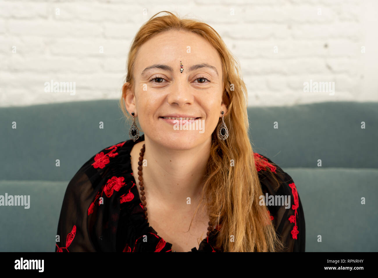 Portrait of beautiful caucasian woman with a bindi in the center of her forehead feeling happy and peaceful with her new healthy and spiritual lifesty Stock Photo