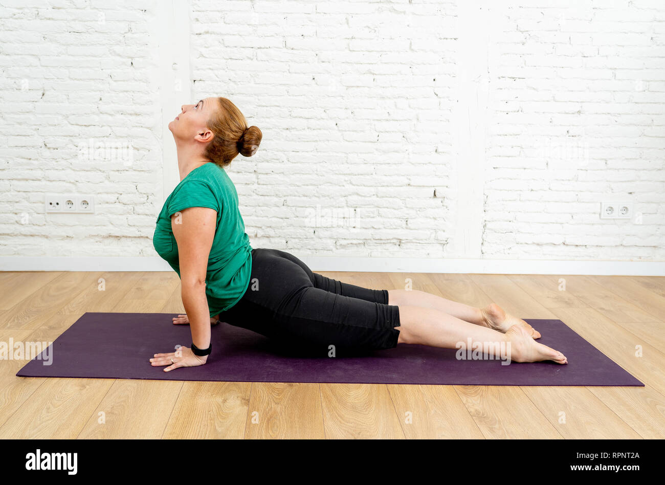 Full length Portrait of young sporty woman working out doing Yoga in Ardha bhudjangasana exercise Baby Cobra pose wearing casual sportswear at modern  - Stock Image