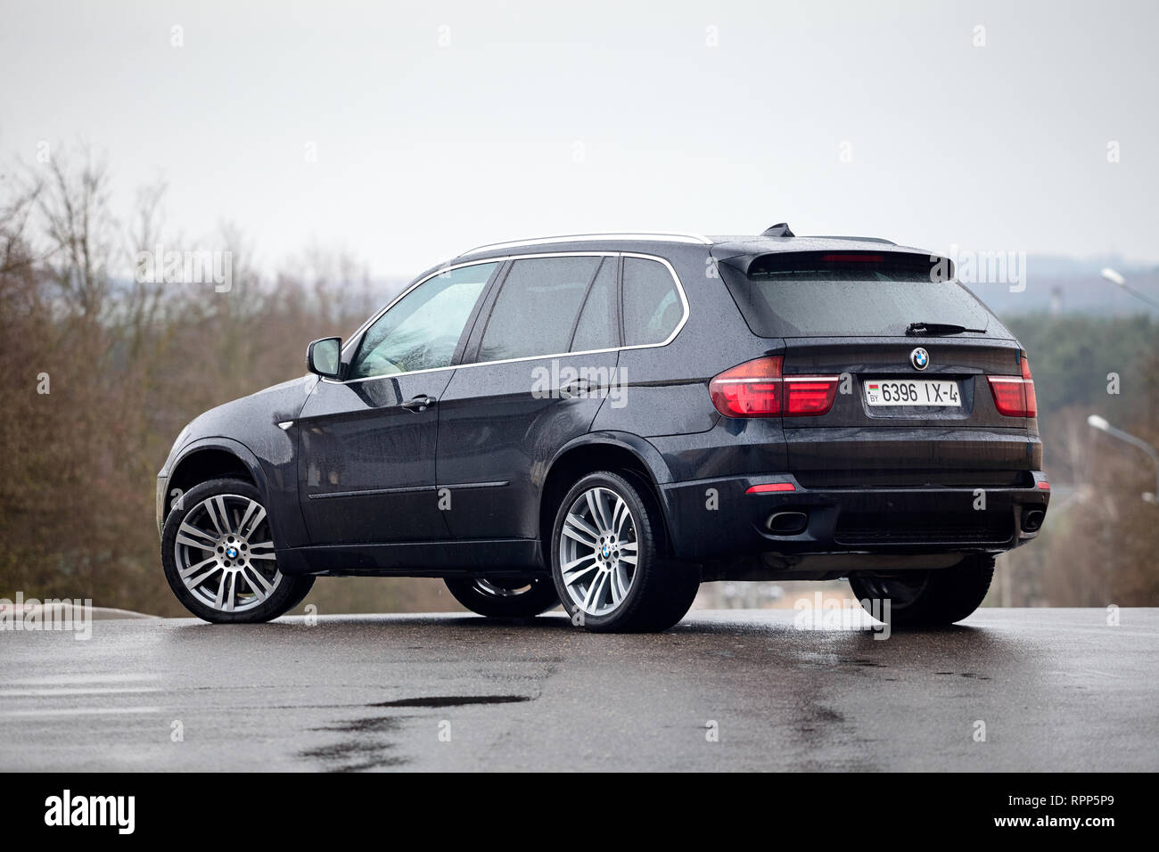 GRODNO, BELARUS - OCTOBER 2016: BMW X5 standing on asphalt under rain covered with raindrops over gray rainy sky and forest background. - Stock Image