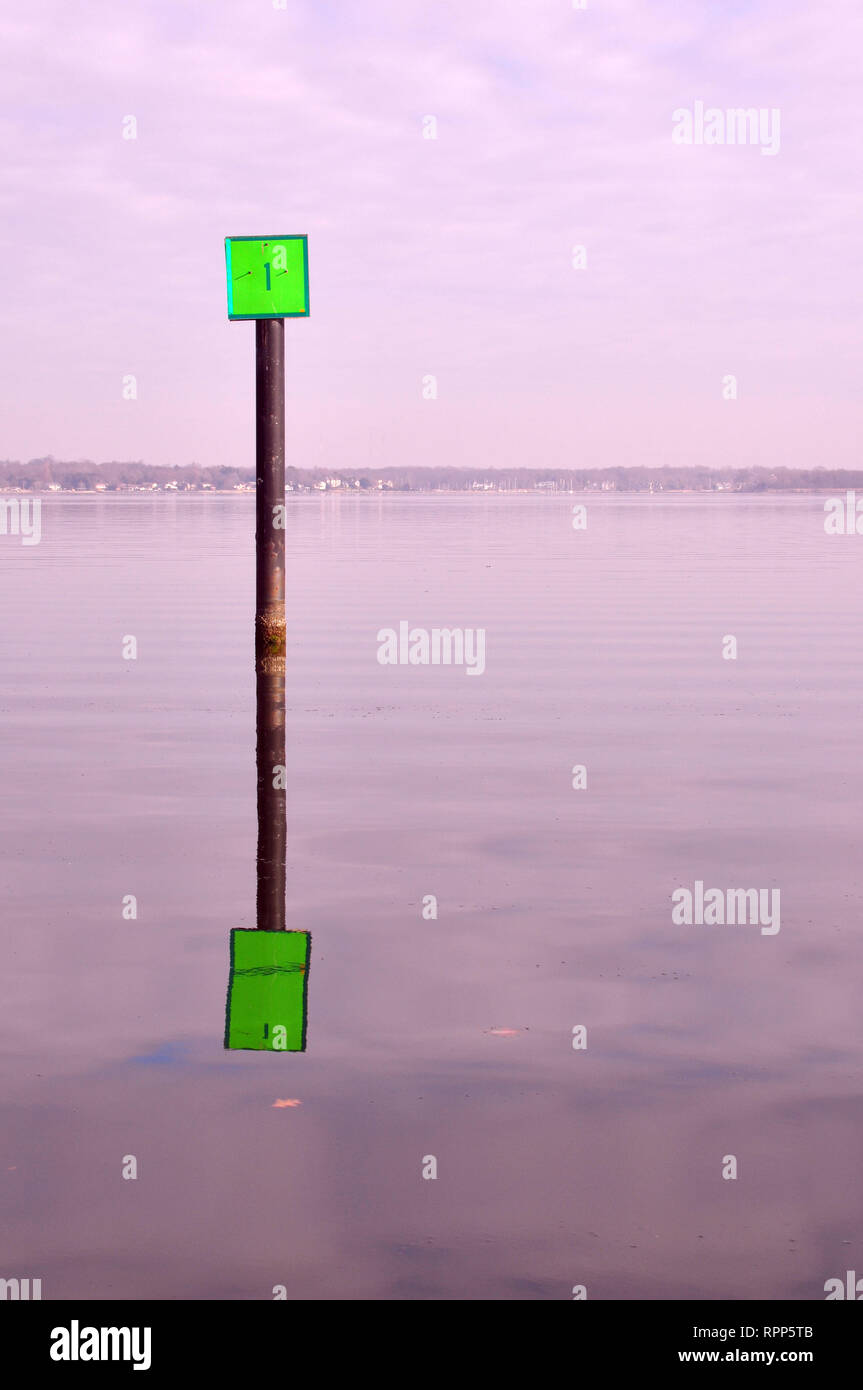 A Green Channel Marker with it's reflection in the Chesapeake Bay Near Annapolis, Maryland - Stock Image