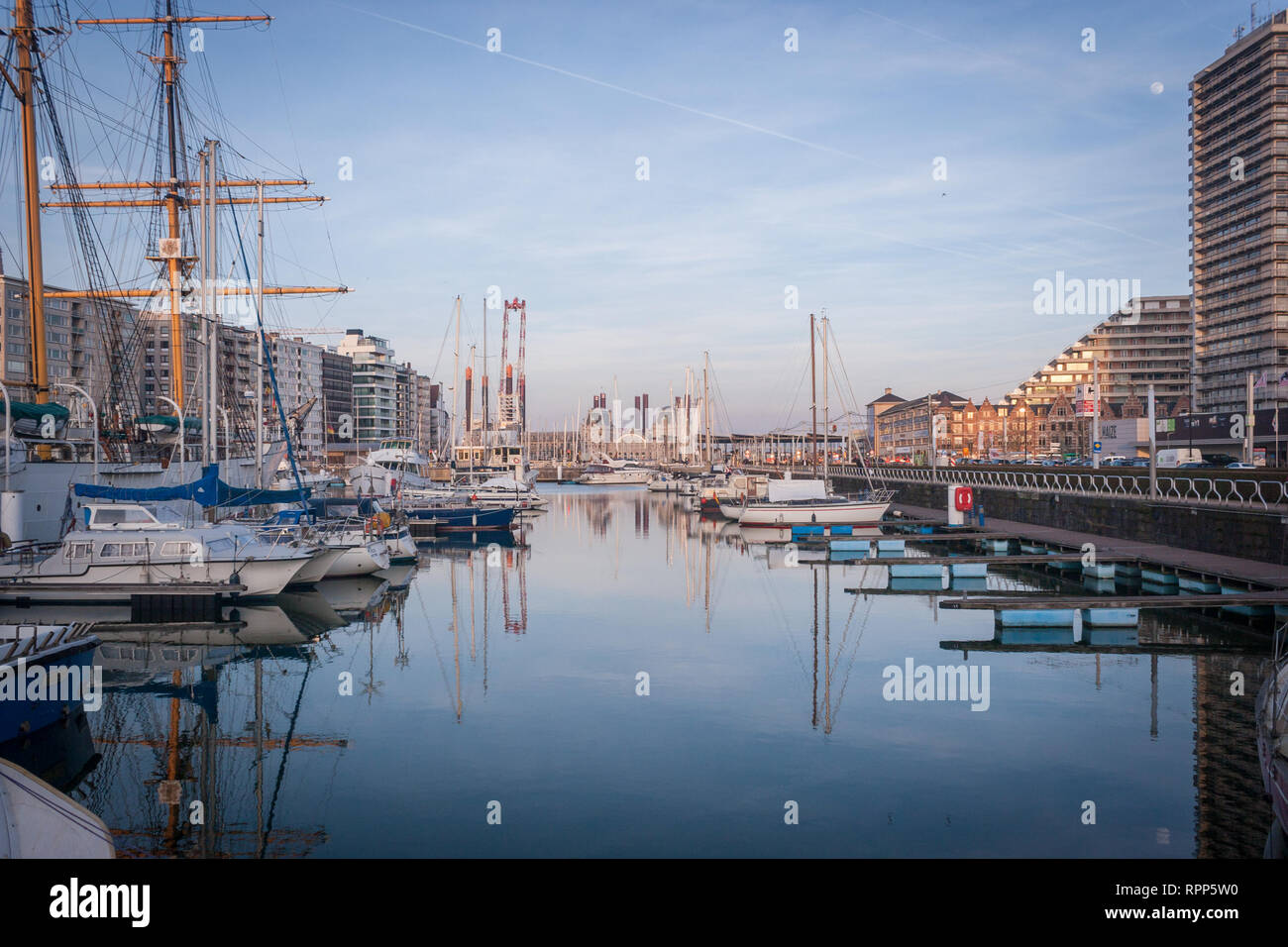 Oostede / Belgium - February 17 2019: The sun sets over the harbor in Oostende during an unusually warm spell that has attracted thousands of visitors. - Stock Image