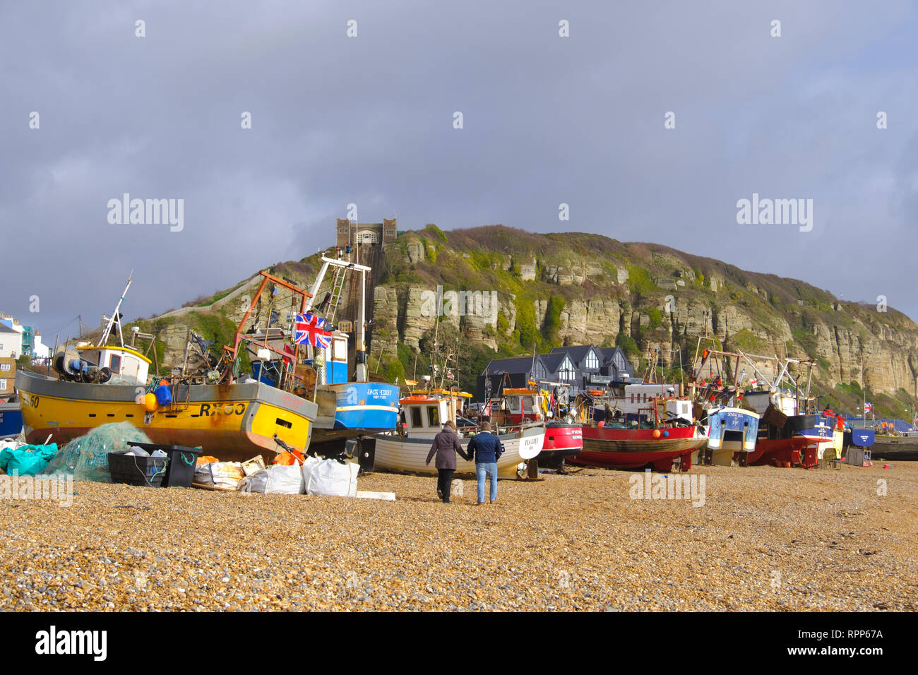Couple strolling past Hastings fishing boats on the Old Town Stade beach on a stormy day in winter, East Sussex, UK Stock Photo
