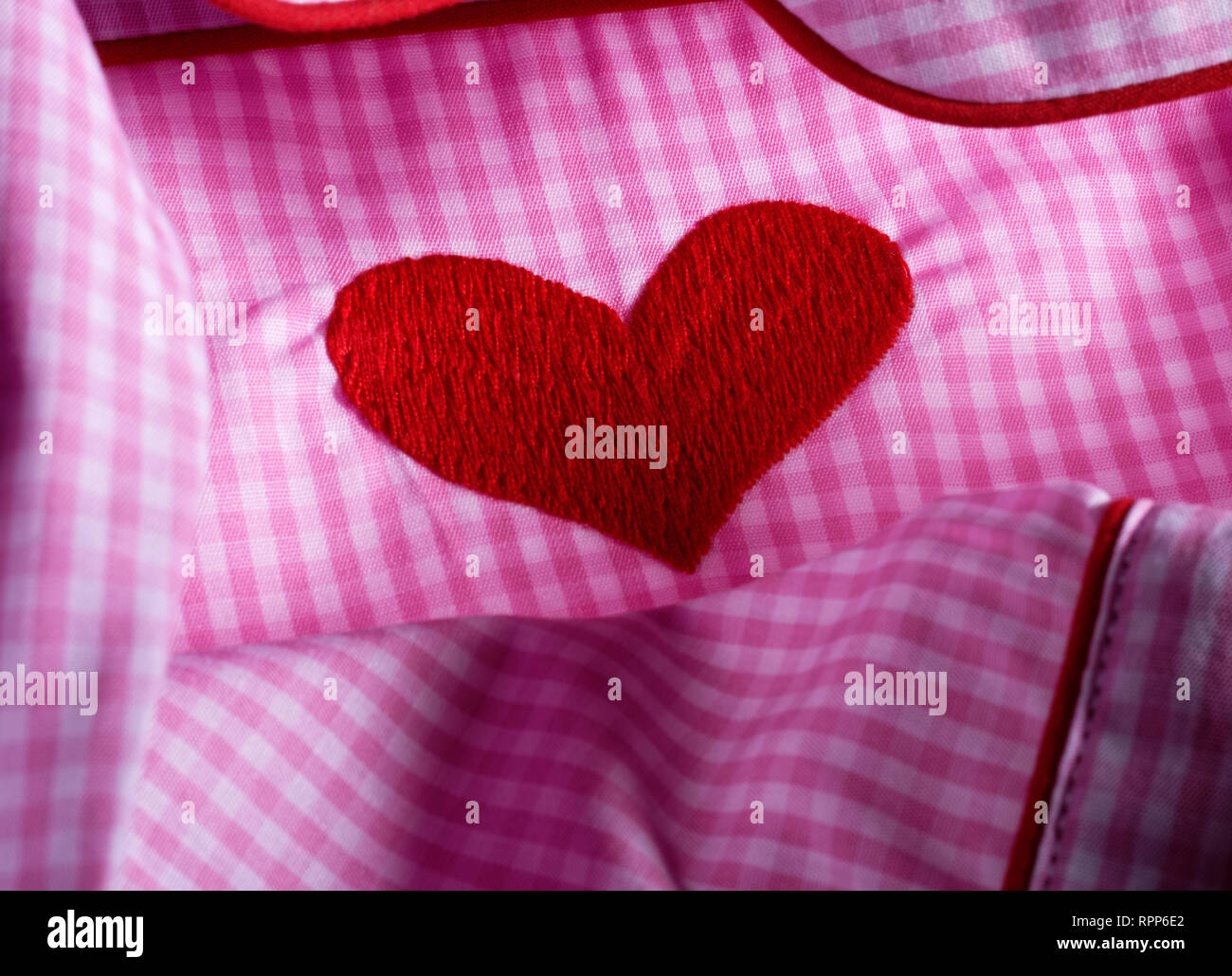Pink and white checked gingham fabric with red heart. Cotton nightwear. Stock Photo
