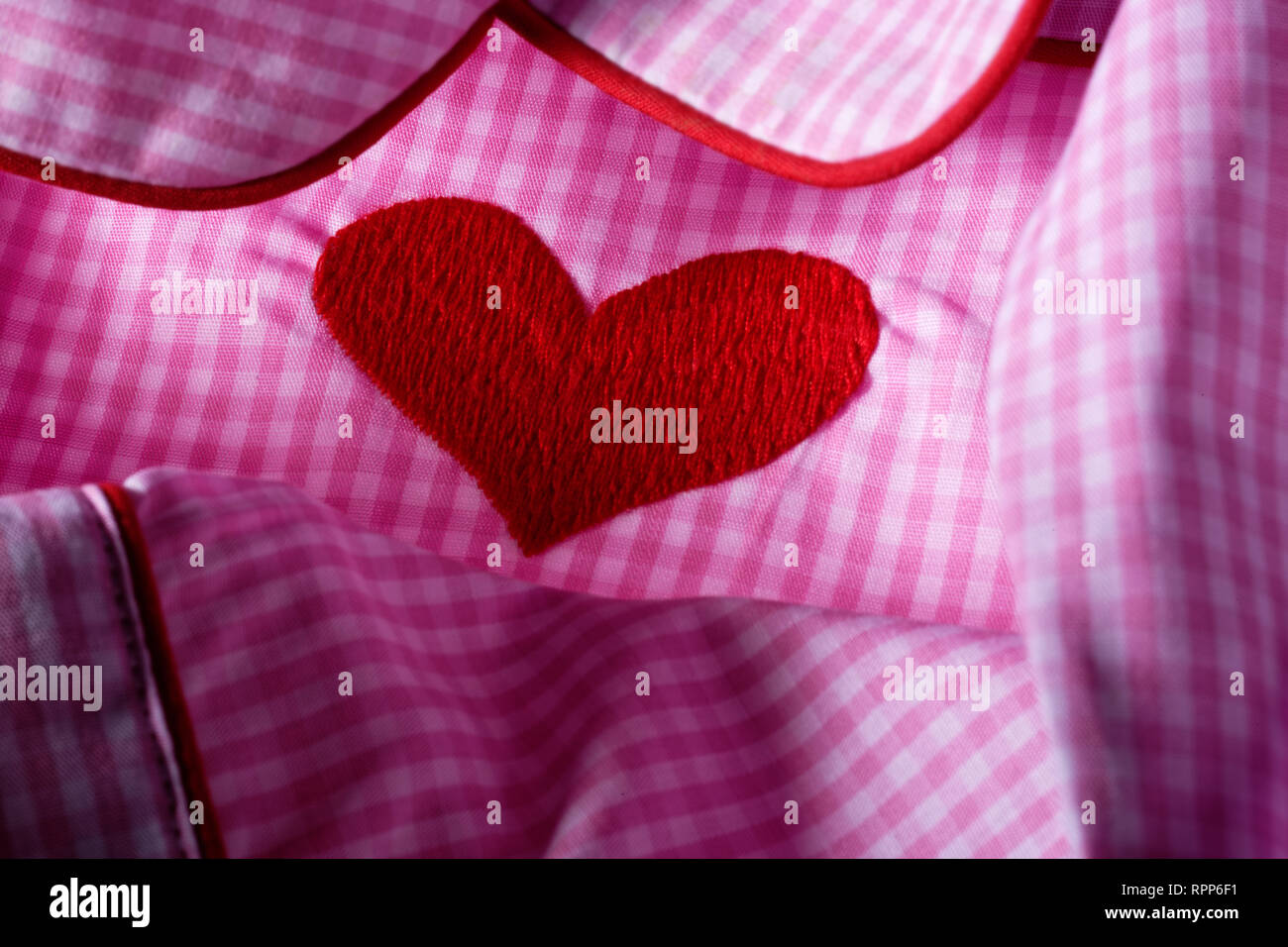 Pink and white checked gingham fabric with red heart. Cotton nightwear. - Stock Image