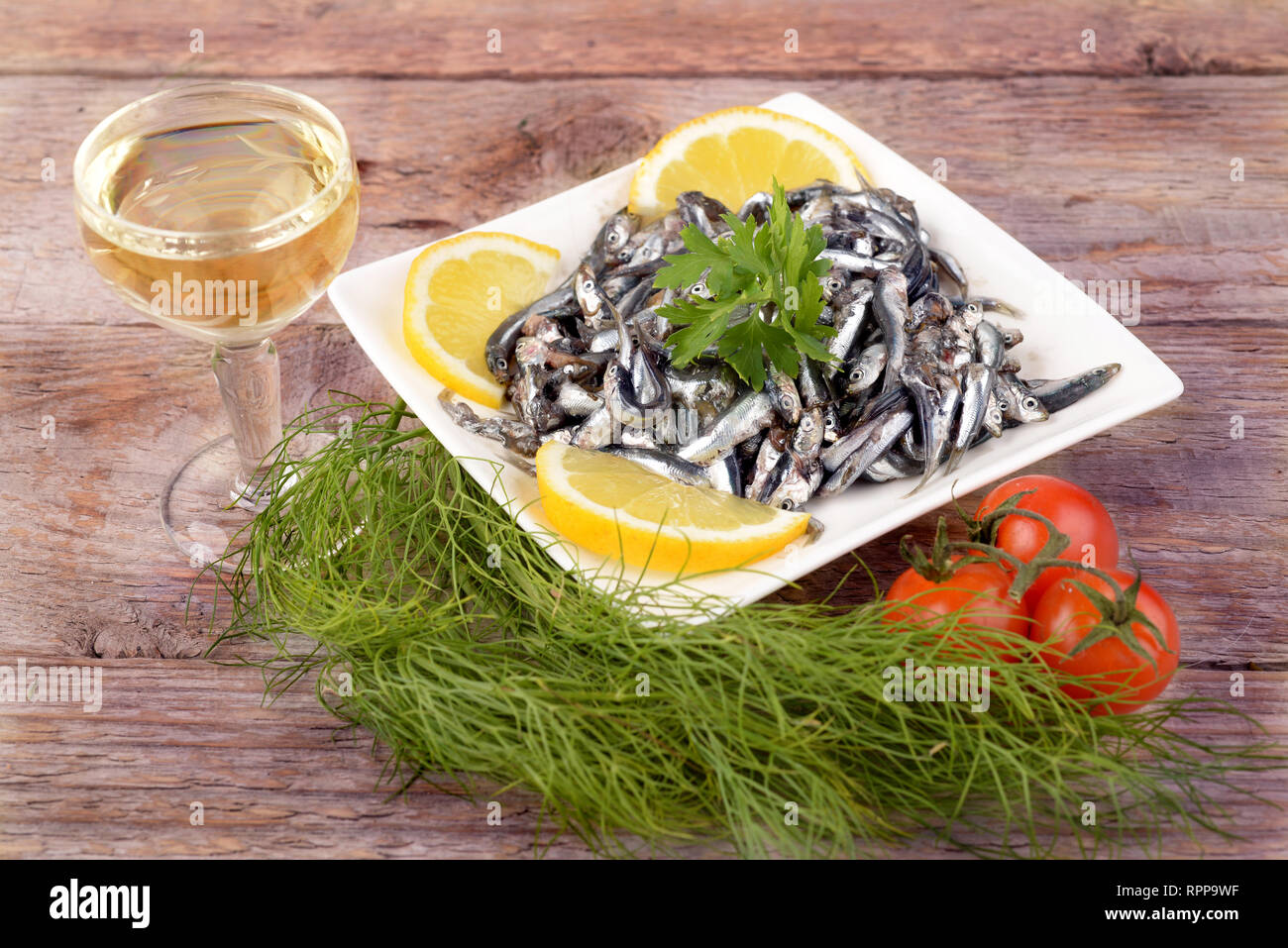 white plate with lemon and wine anchovies on wooden table - Stock Image