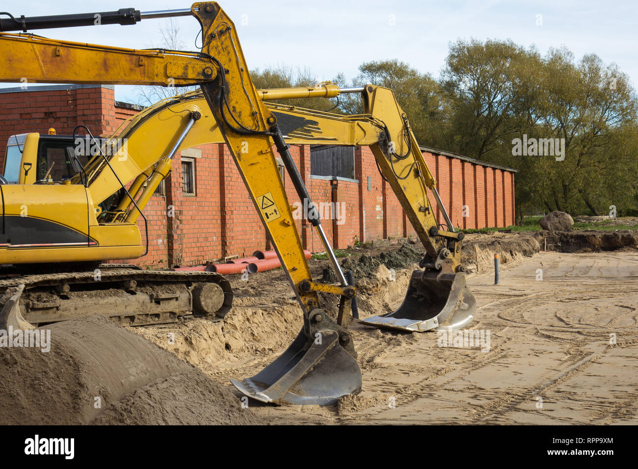 two yellow excavators parked at construction site - Stock Image