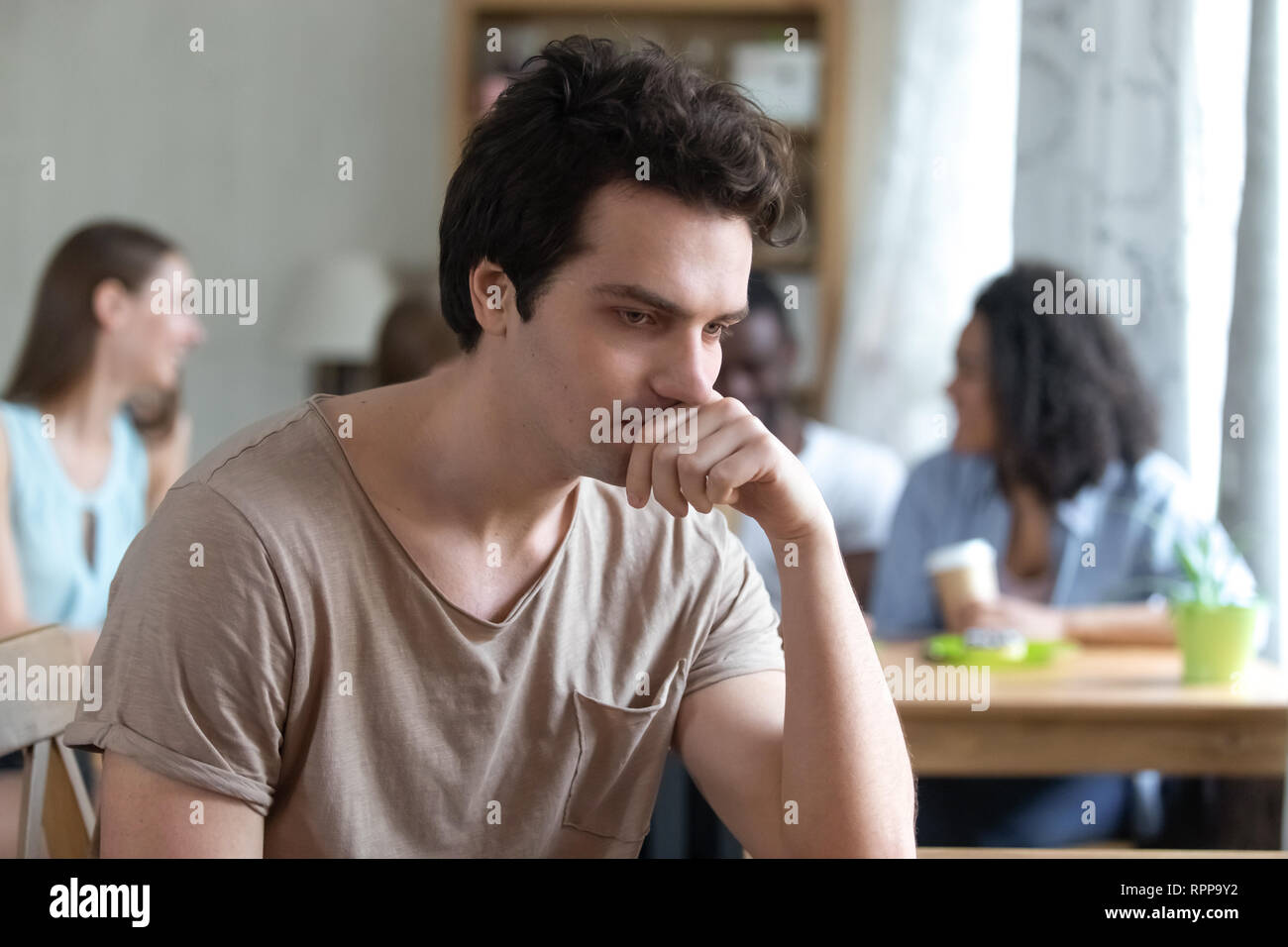 Upset thoughtful man sitting alone, low self-esteem, have no friends - Stock Image