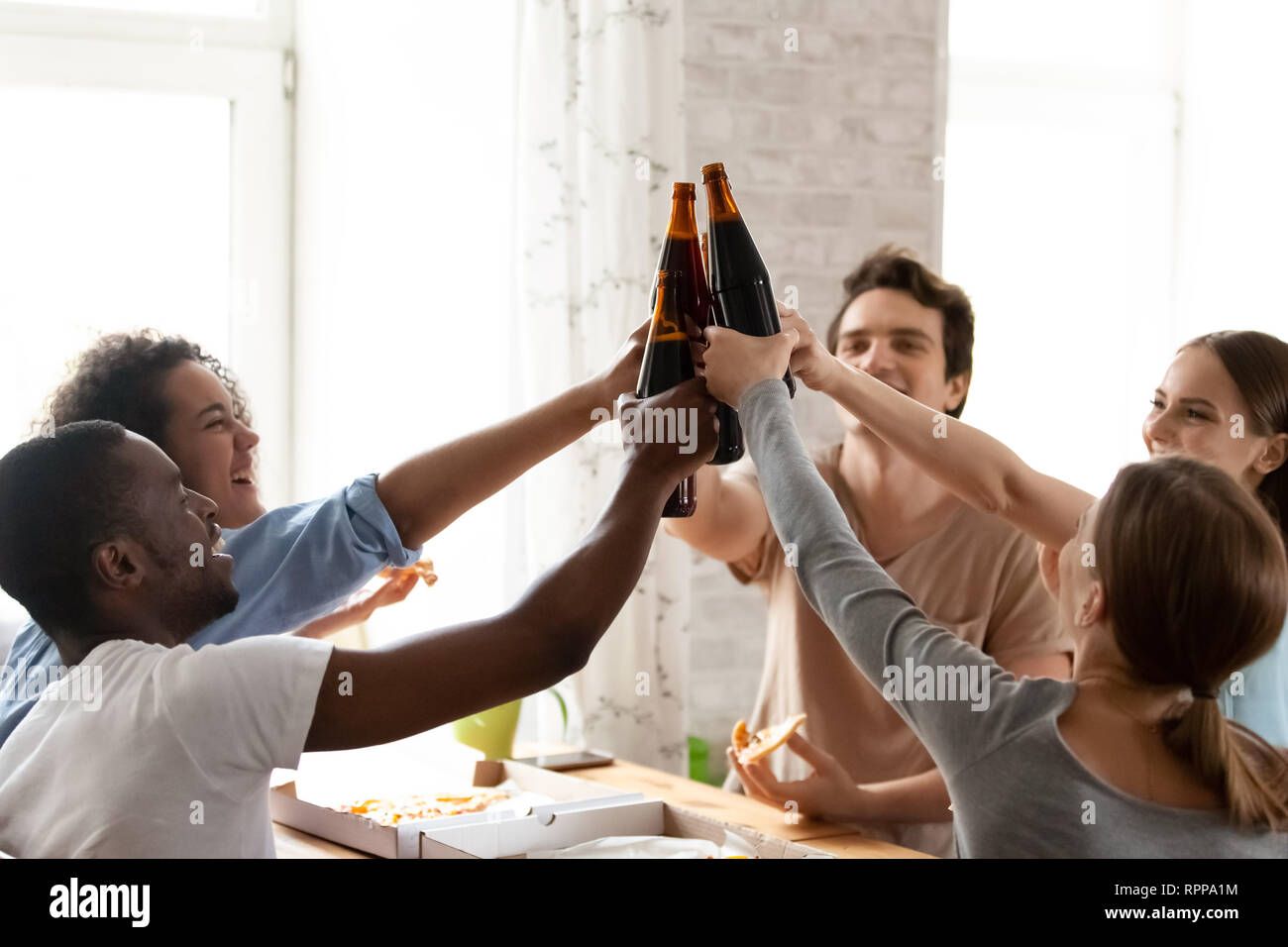 Happy multiracial people celebrate success, clinking bottles in bar - Stock Image