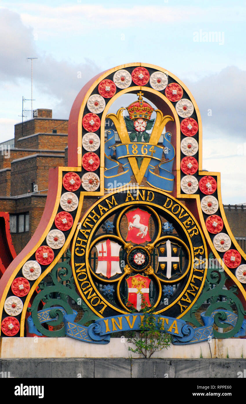 The colorful and fancifully designed emblem of the historic London Chatham Dover Railway.  The growing vegetation is symbolic of a bygone era. - Stock Image