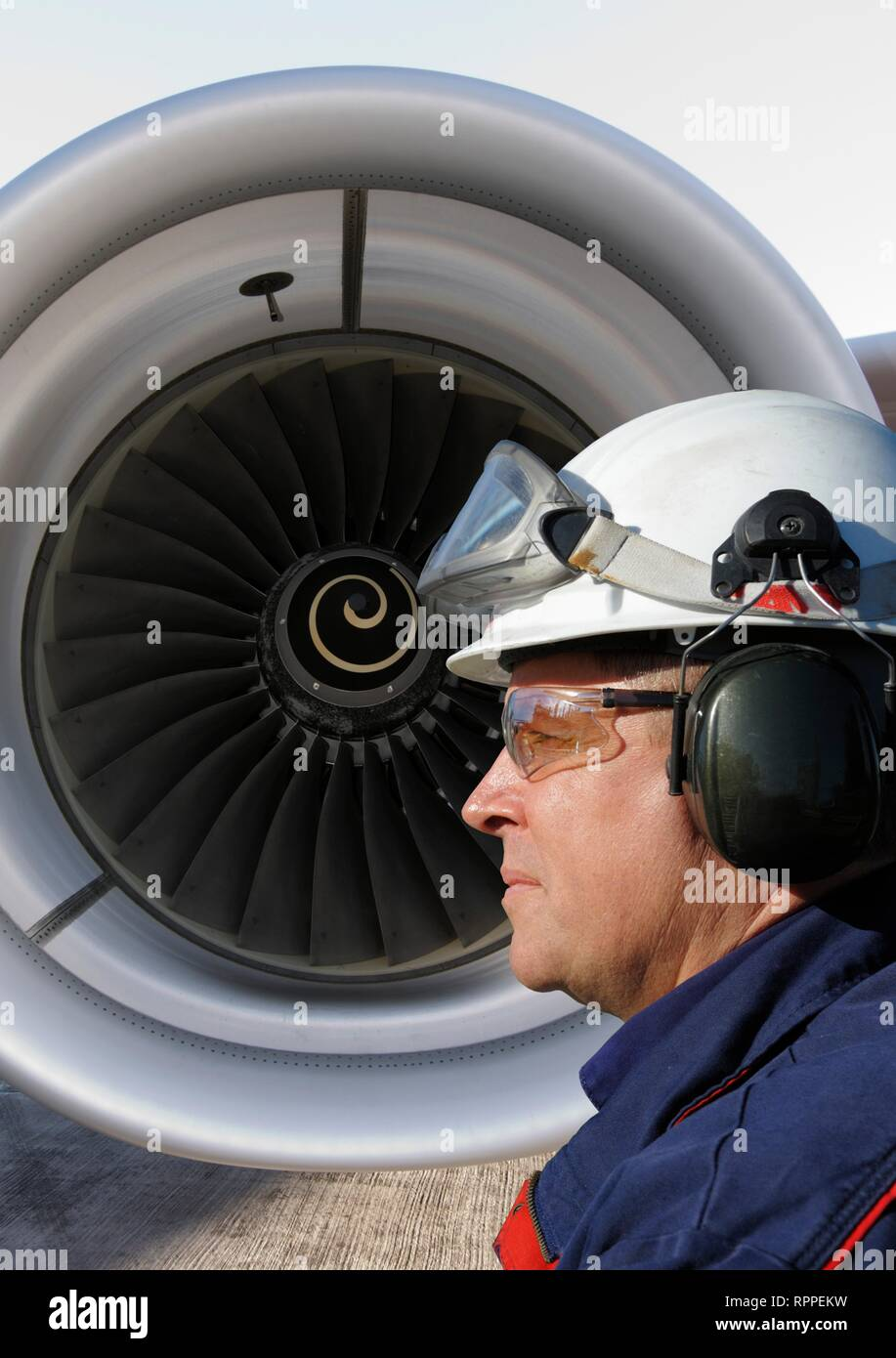 Airplane mechanic standing in front of a jumbo jet's engine. - Stock Image