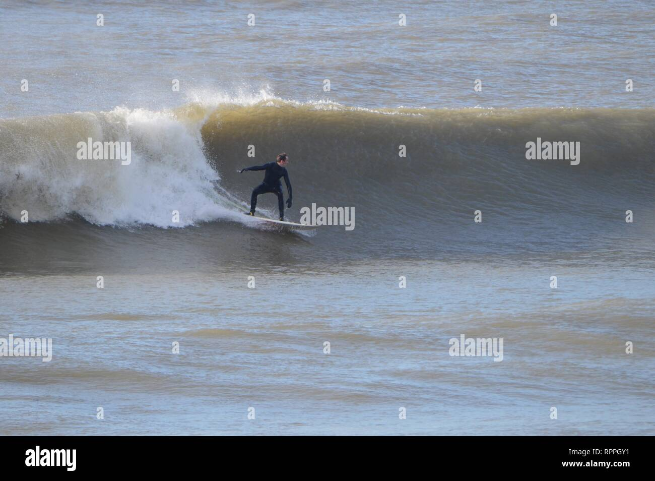 Aberystwyth Wales UK. Friday 22 Feb 2019 UK weather: Surfers enjoying the incredibly warm February sunshine in Aberystwyth on the west coast of Wales. The weather is forecast to remain fine for the next few days with the chance of record breaking temperatures in some places photo Credit: keith morris/Alamy Live News - Stock Image