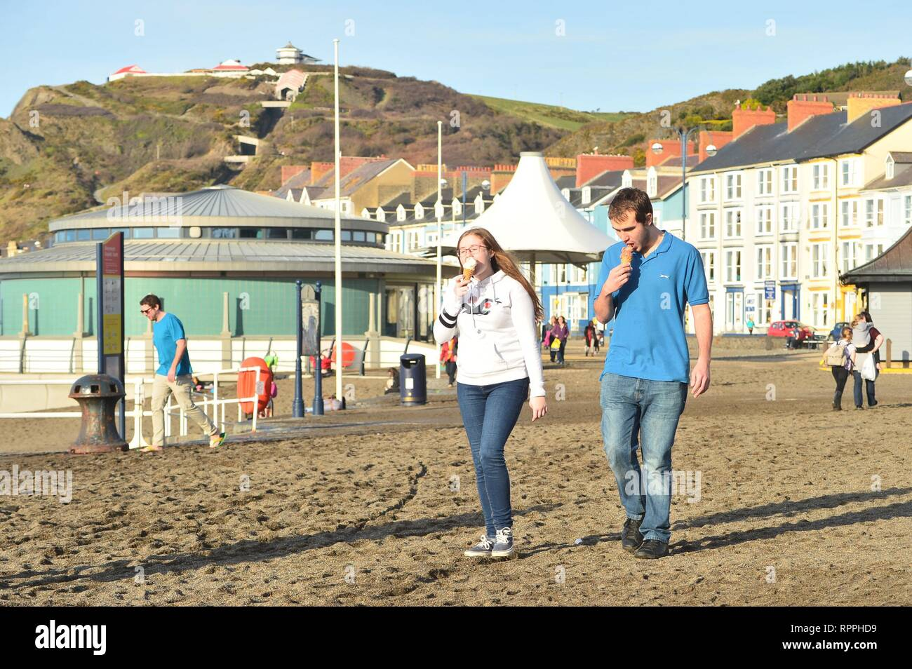 Aberystwyth Wales UK. Friday 22 Feb 2019 UK weather: Peopke enjoying the incredibly warm February sunshine in Aberystwyth on the west coast of Wales. The weather is forecast to remain fine for the next few days with the chance of record breaking temperatures in some places photo Credit: Keith Morris/Alamy Live News - Stock Image