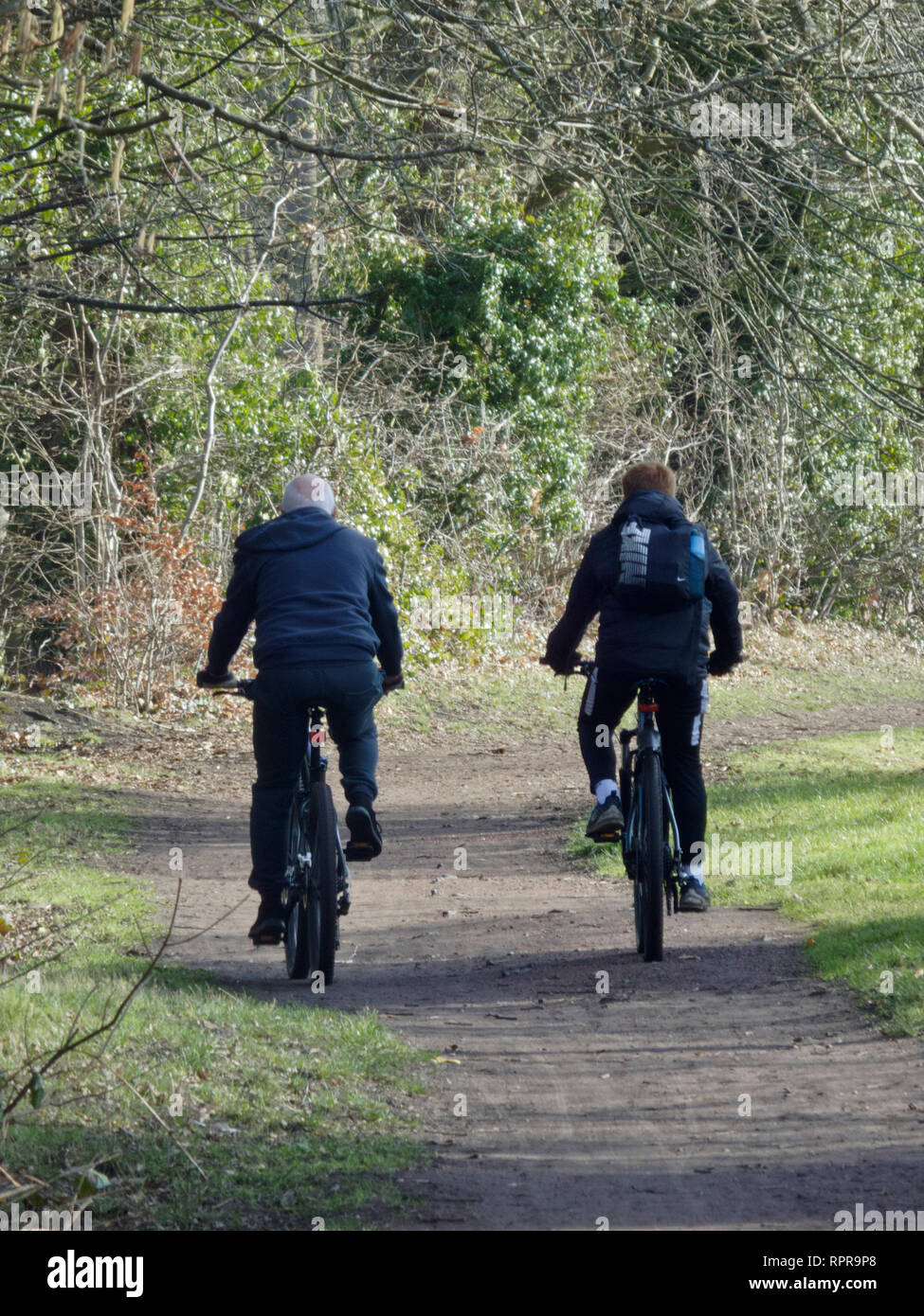 Caucasian Grandfather & Grandson Cycling Along a Canal Towpath in Winter, UK - Stock Image