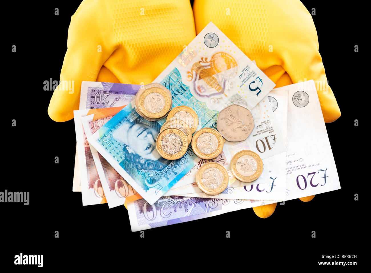 A pair of hands wearing yellow rubber gloves holding pound notes & coins. Concept cash in hand, black economy or low pay. - Stock Image