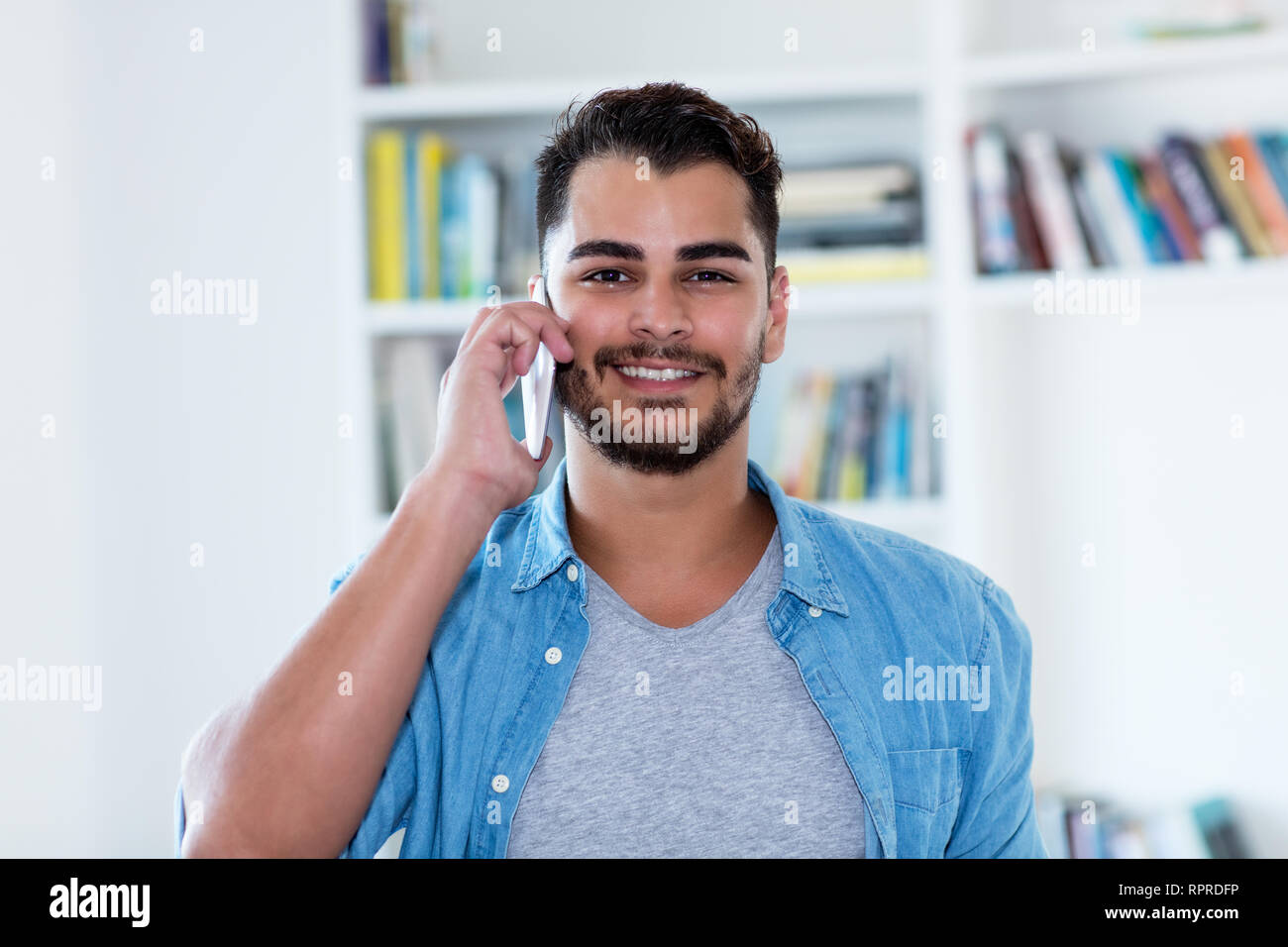Laughing mexican hipster man with beard at phone indoor at home - Stock Image