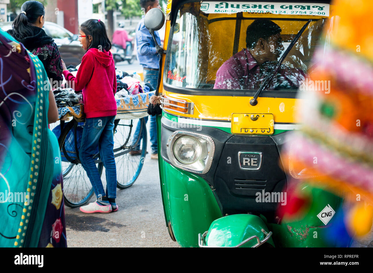 Green and yellow auto rickshaw stopping for passengers in Ahmedabad gujarat - Stock Image
