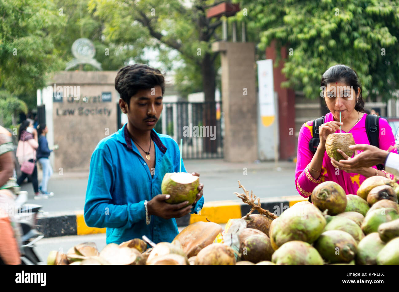 Coconut vender peeling a nut while an india lady sips  - Stock Image