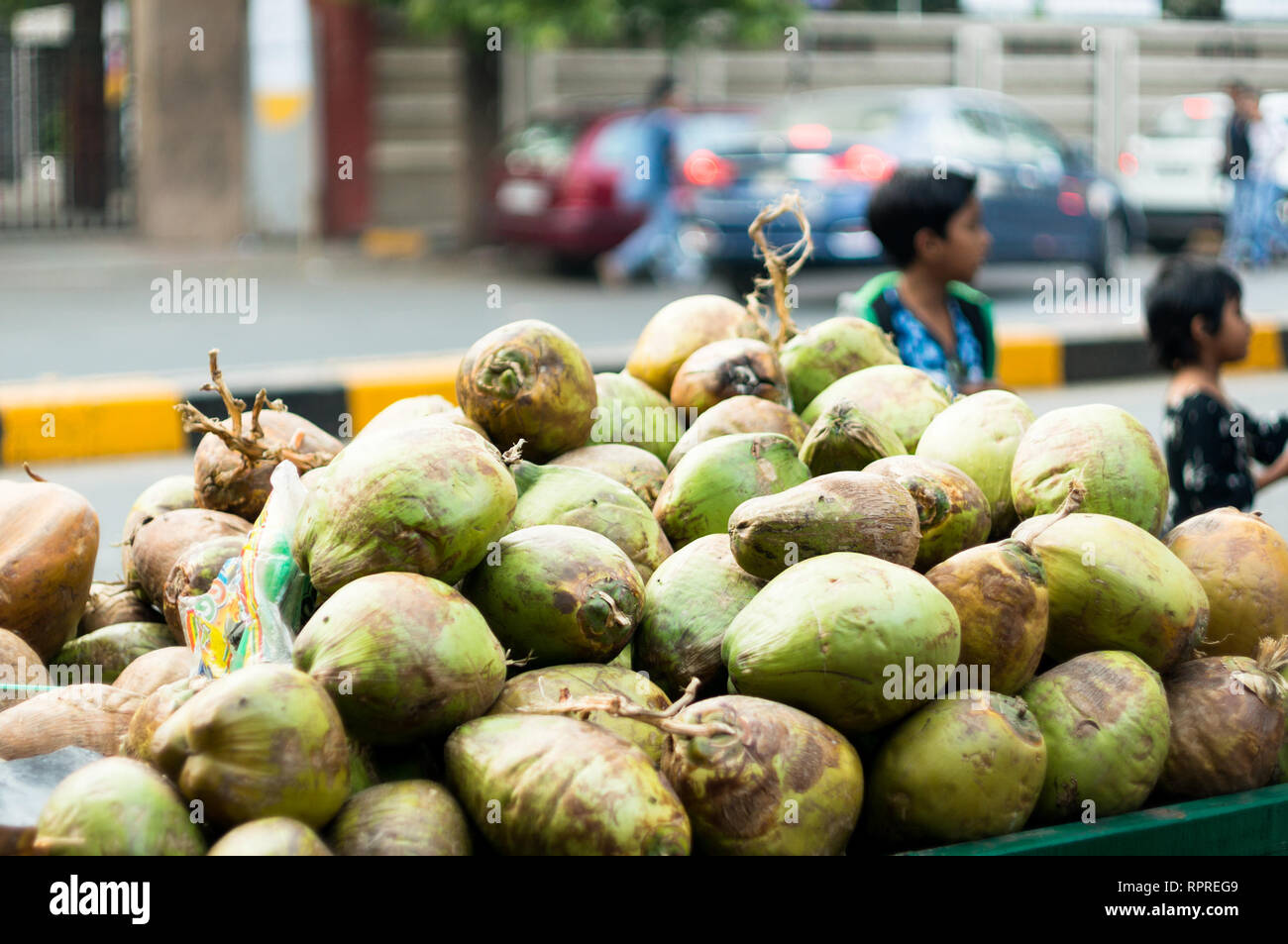 coconut cart on the roadside with children playing in the background - Stock Image