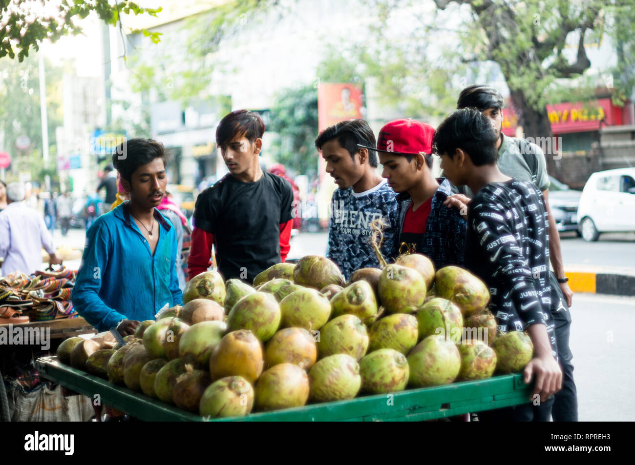 Coconut vendor and cart surrounded by people eager to drink - Stock Image