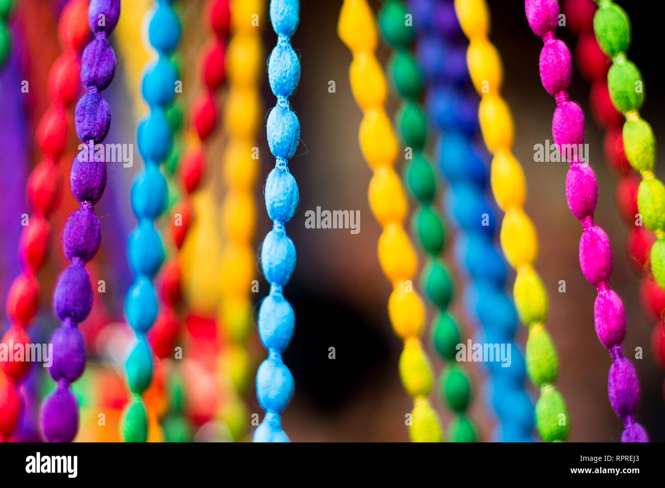 Multicolored braided strings hanging tight with a blurred background - Stock Image