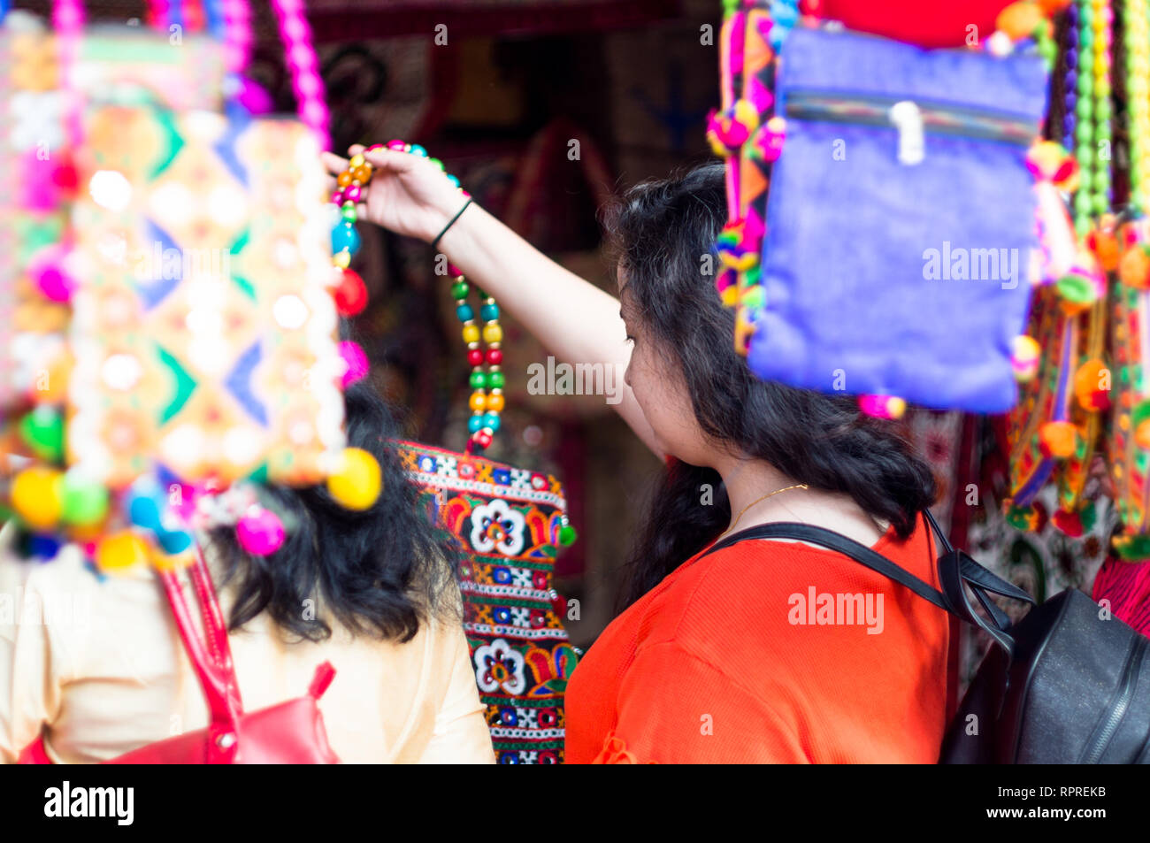 Indian lady with long black hair and red shirt shopping in a handicraft store in Gujarate - Stock Image