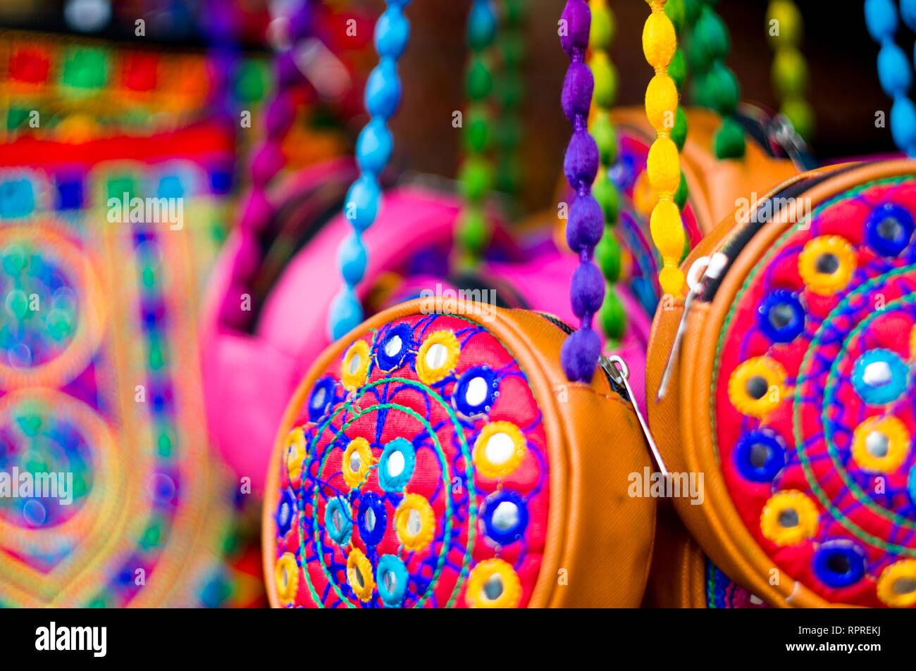 Colorful, textile, hand made hand bags hanging in a shop in Gujarat  - Stock Image