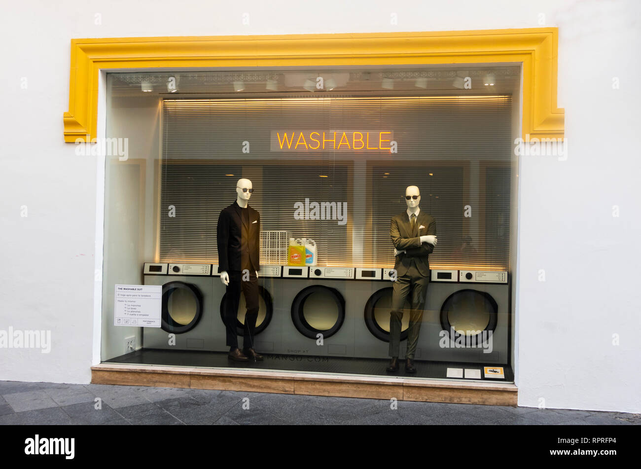 Window display featuring washable men's suits in Seville, Spain - Stock Image