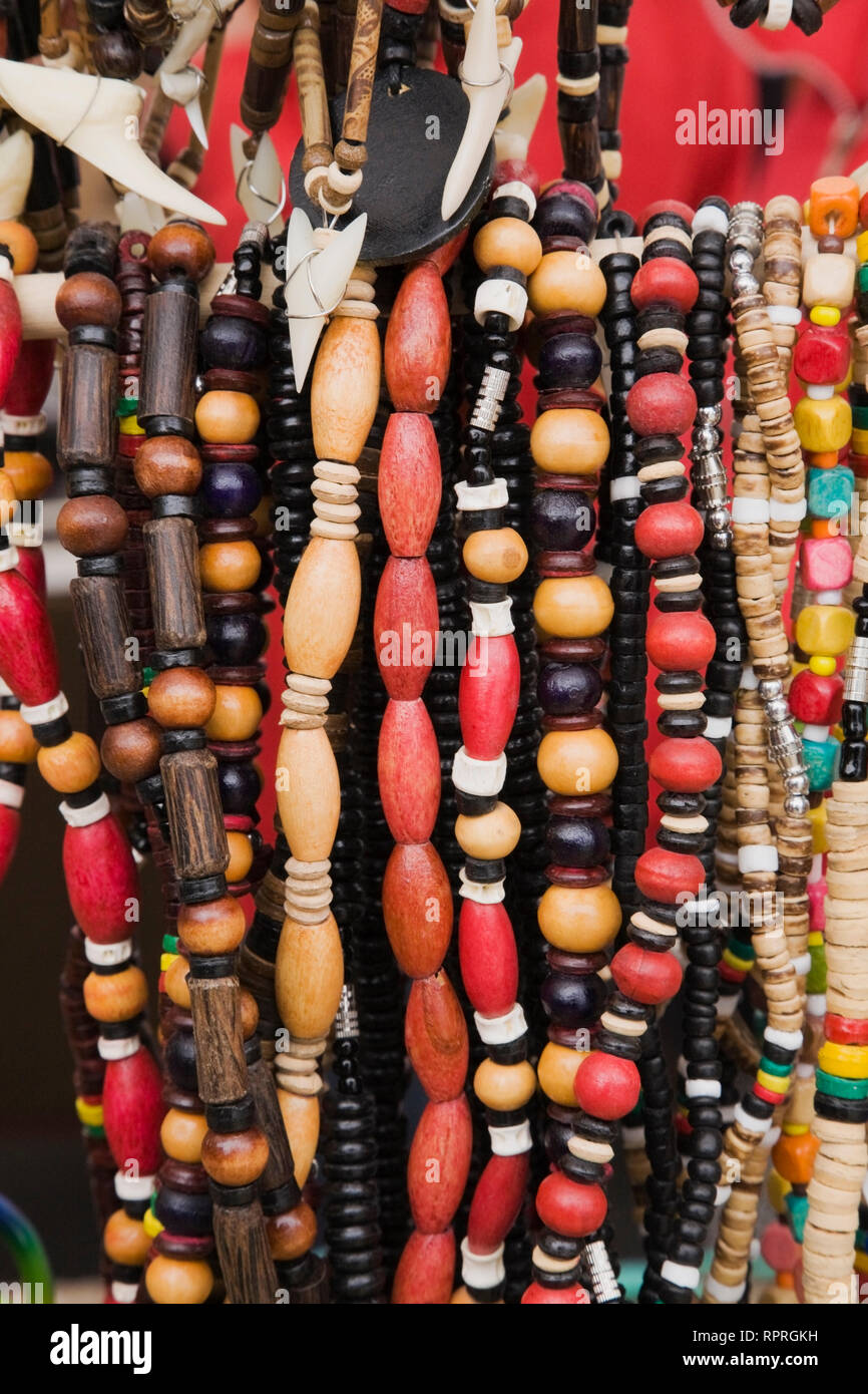 Close-up of wooden bead necklaces for sale and displayed at an outdoor market - Stock Image