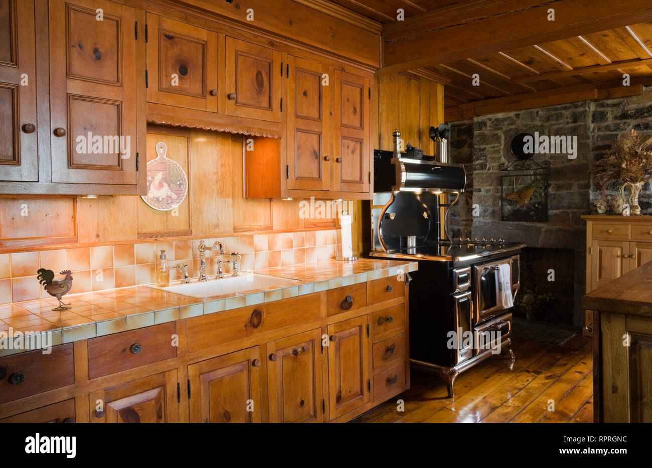 Wooden Kitchen Cupboard Cabinets And Replica Of An Antique Stove In The Kitchen Of An Old Circa 1750 Canadiana Fieldstone Home Stock Photo Alamy