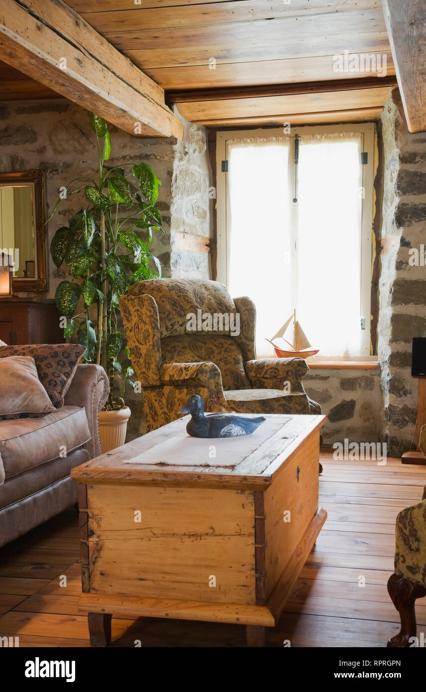 Antique storage chest coffee table, sofas, chairs and furnishings in living room of old 1772 Canadiana cottage style fieldstone and wooden siding home - Stock Image
