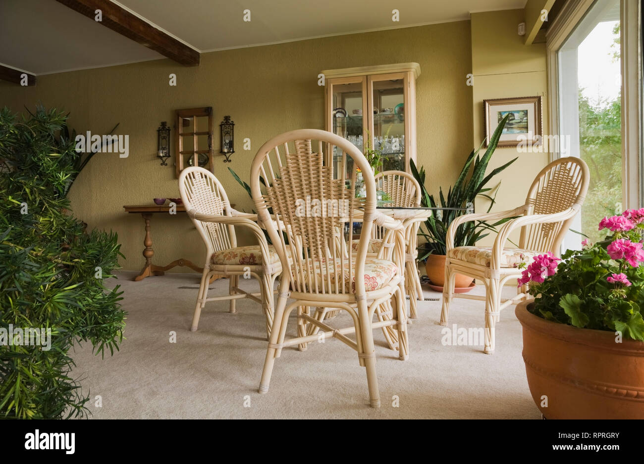 Wicker table, chairs and furnishings in the dining room of an old Canadiana and French manoir cottage style home - Stock Image