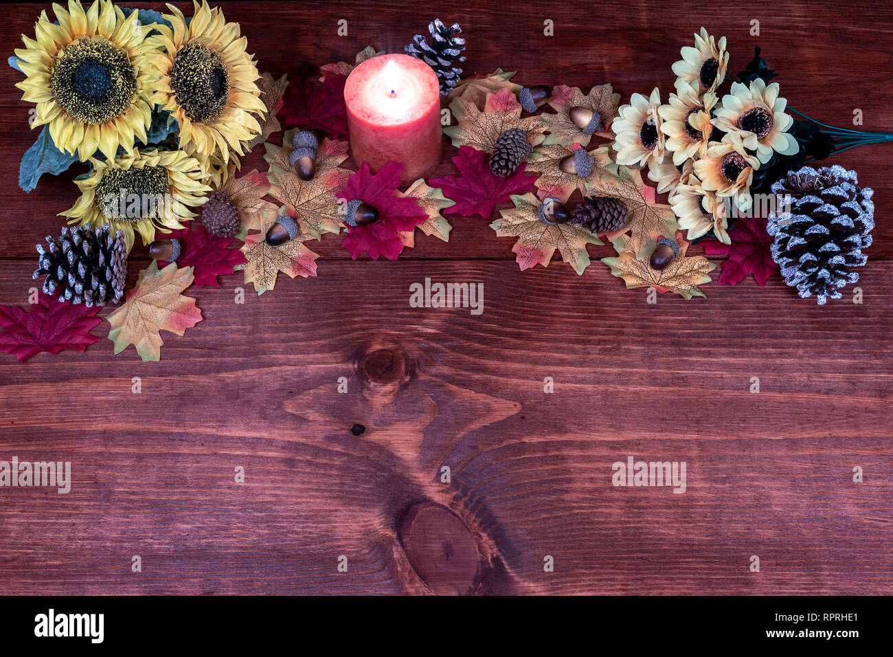 Thanksgiving decor with candle, frosted pine cones, sunflowers, acorns and maple leaves Stock Photo