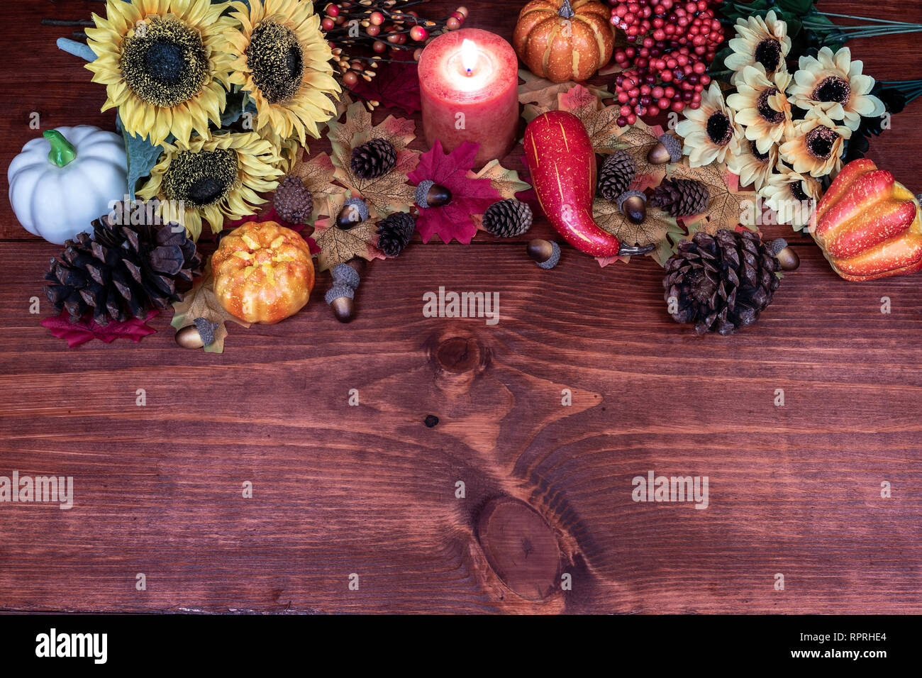 Thanksgiving decor with candle, pine cones, sunflowers, acorns, pumpkins, squash, guard, berries and maple leaves Stock Photo