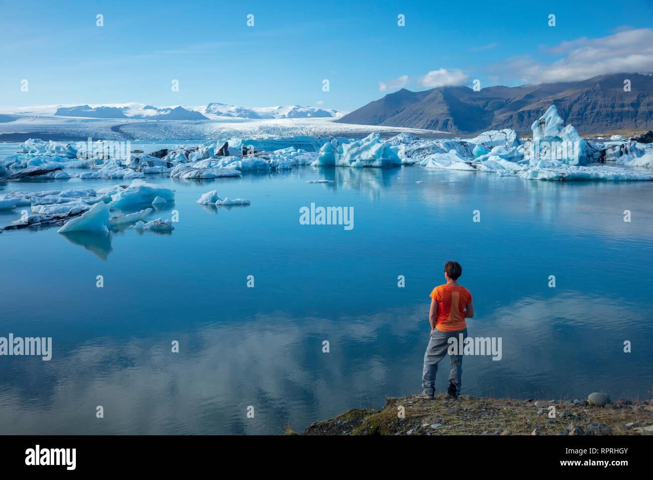 Person on the shore of Jokulsarlon glacier lagoon, beneath Vatnajokull glacier. Vatnajokull National Park, Sudhurland, south east Iceland. Stock Photo