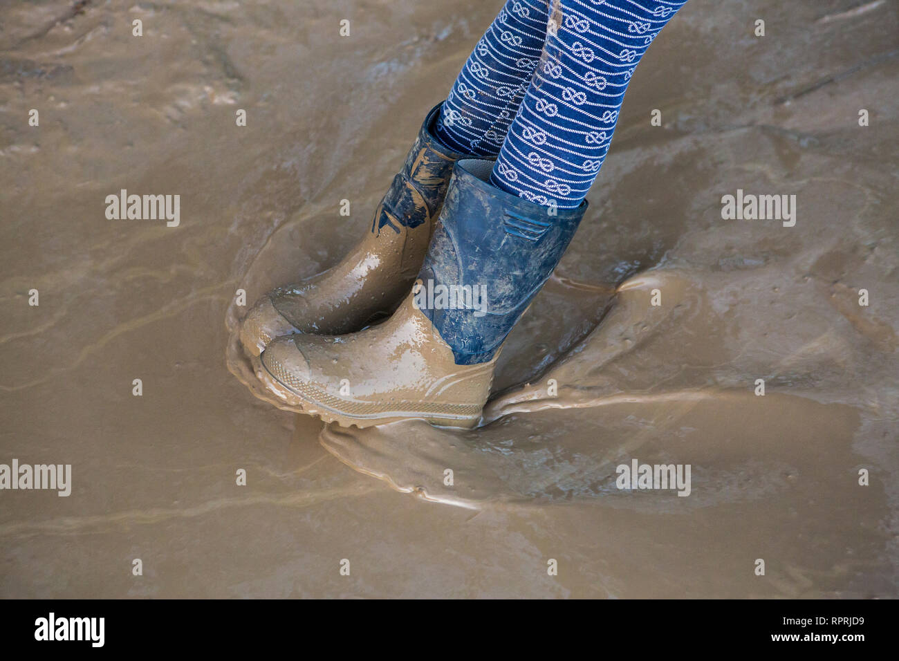 Muddy wellies in a muddy puddle, Sussex, UK Stock Photo