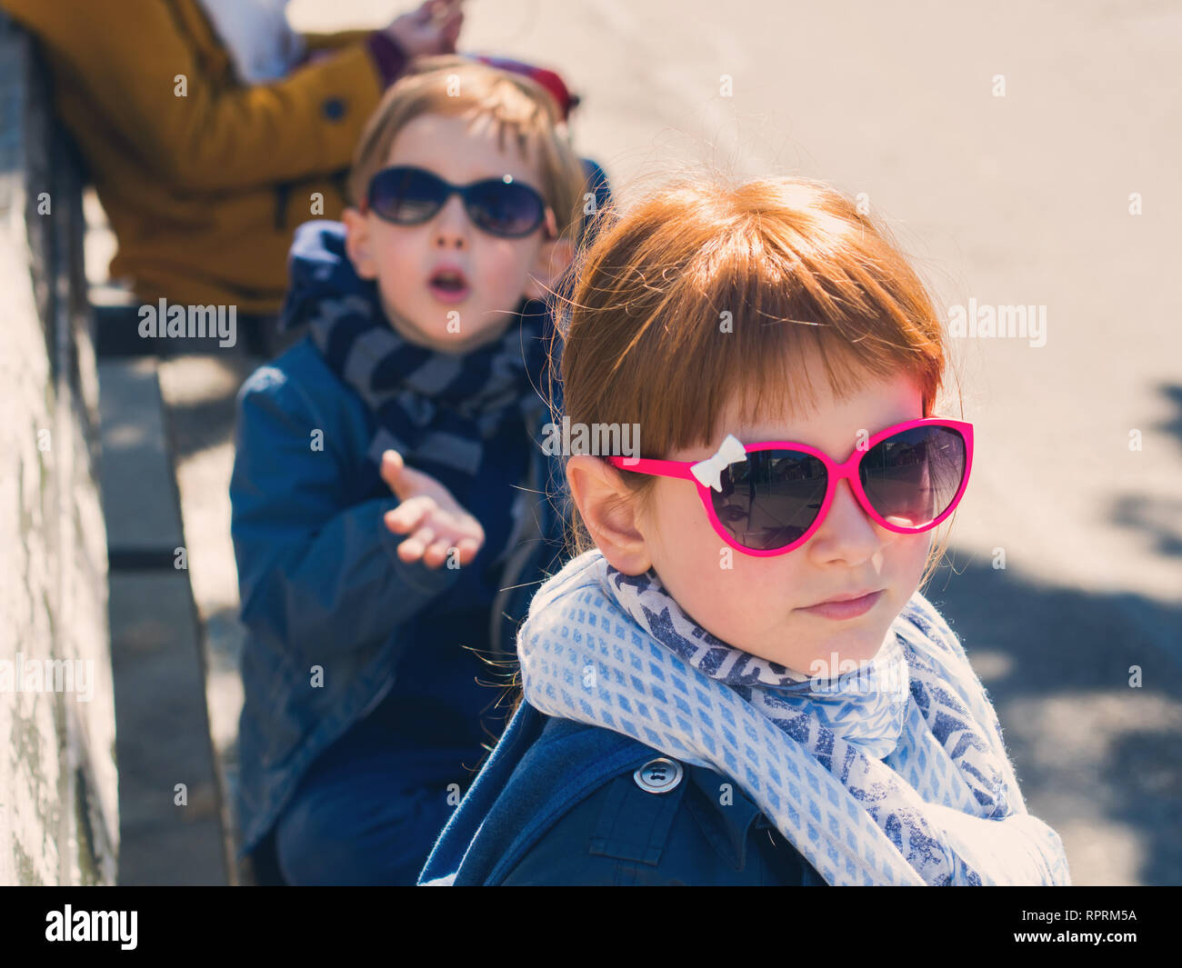 ce39dc0fc2c6 Little funny blonde boy and redhead girl outdoors with funny sun glasses.  Boy sending a kiss with hand