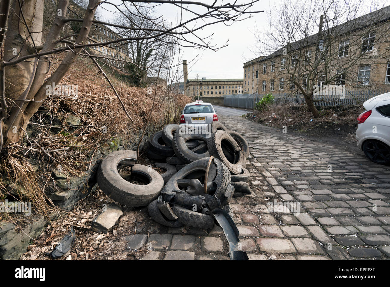 Illegal fly tipping at Dean Clough, Halifax, West Yorkshire, UK - Stock Image