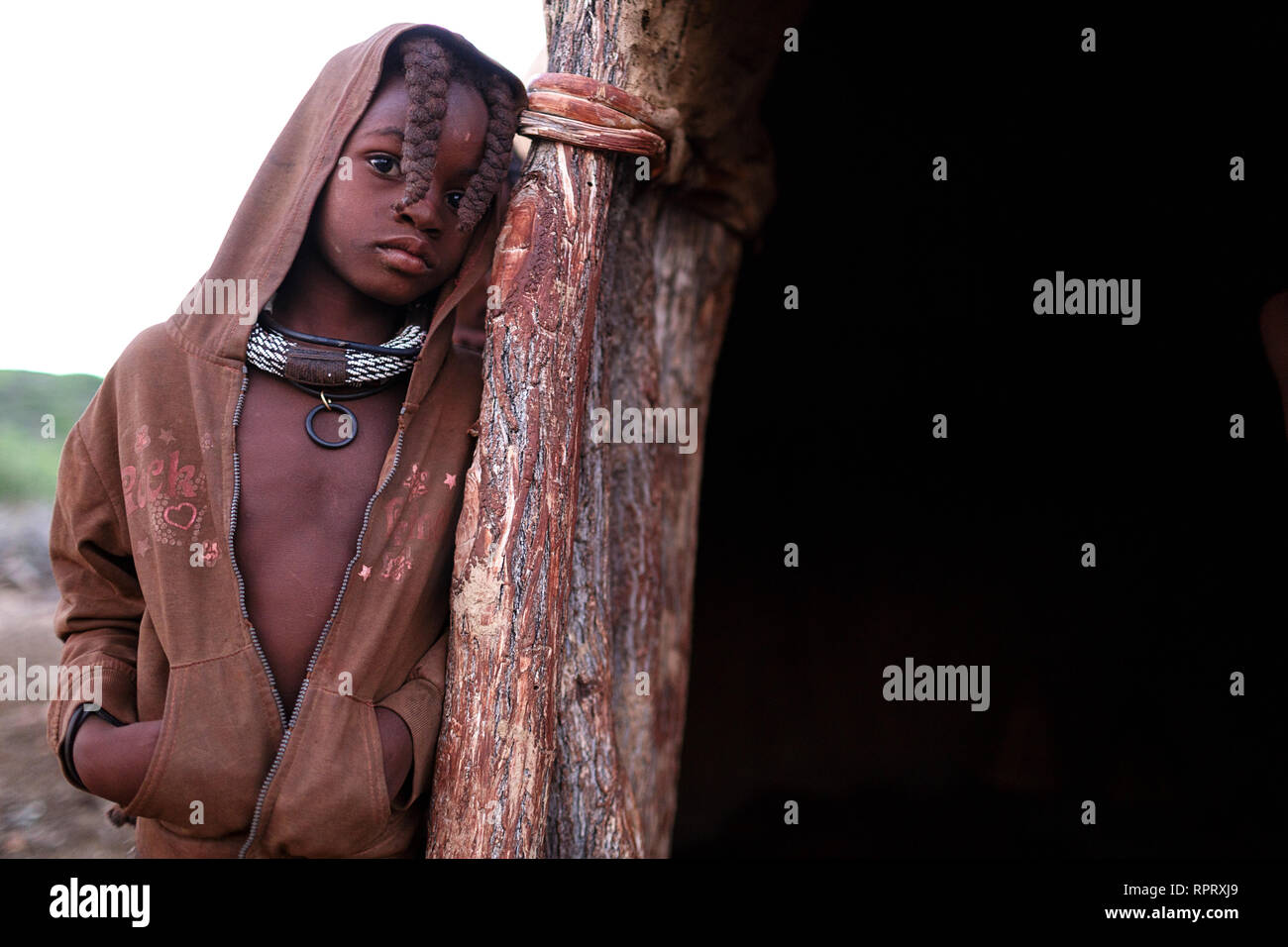 Himba girl with two braids and jewellery, portrait, Himba hut, Himba village, Northern Namibia - Stock Image