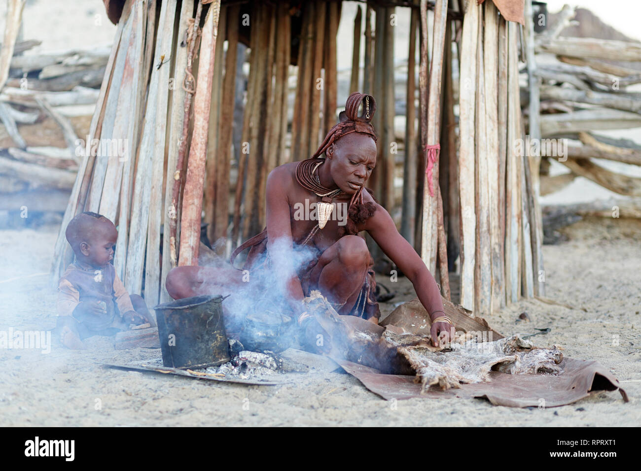 Himba woman and a baby sitting in front of the hut making dinner on fire in a traditional village in Northern Namibia - Stock Image