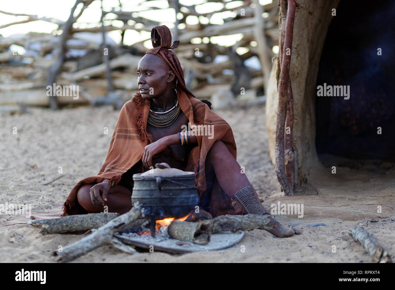 Himba woman sitting in front of the hut making dinner on fire in a traditional village in Northern Namibia - Stock Image