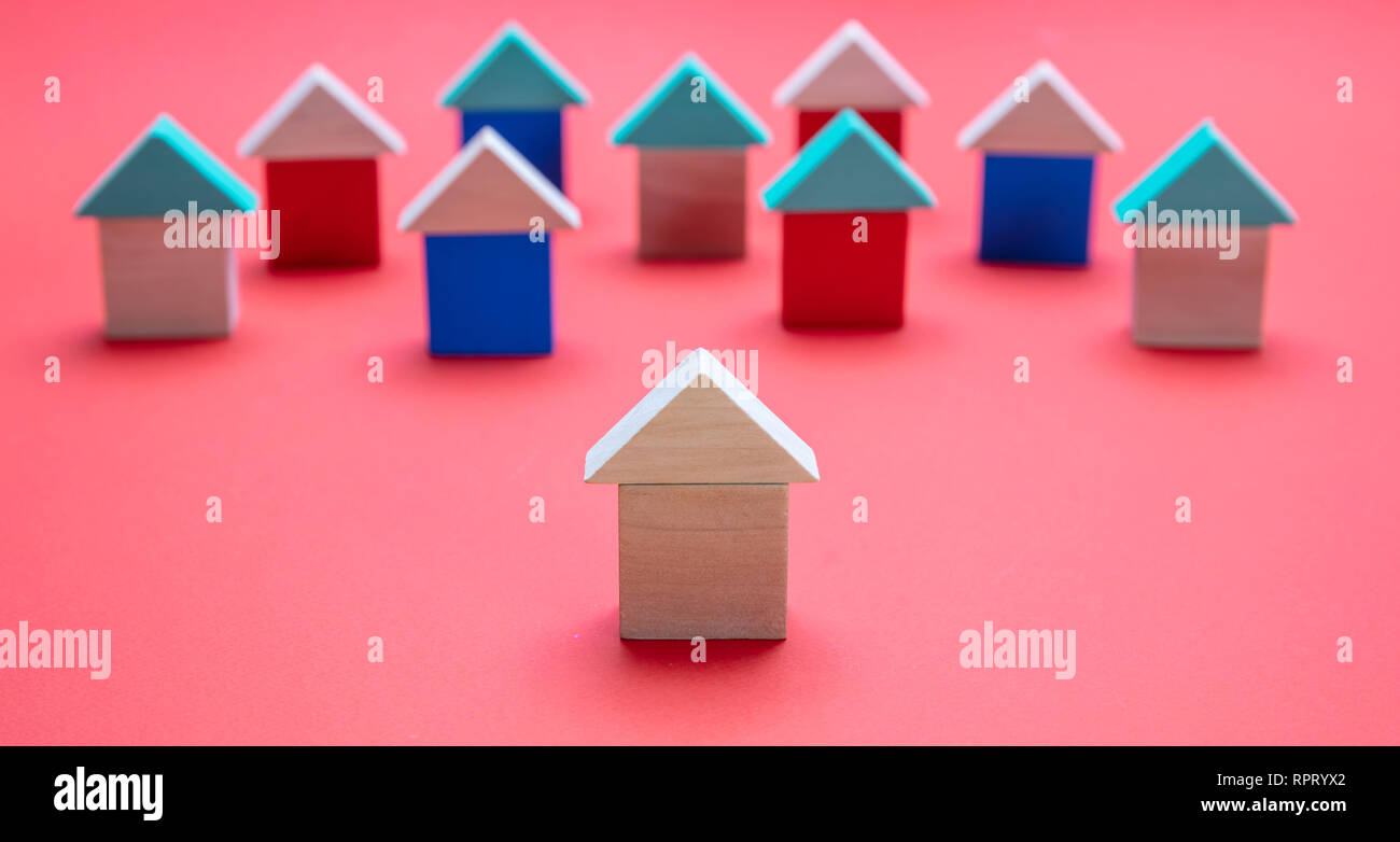 Real estate and standing out concept, One house model ahead of the others, red color background Stock Photo