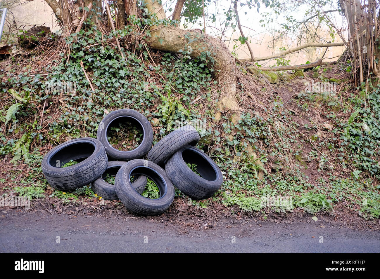 A pile of discarded, car tyres, illegally fly tipped on a country road. this fly tipping has a big impact on environmental damage in the countryside - Stock Image